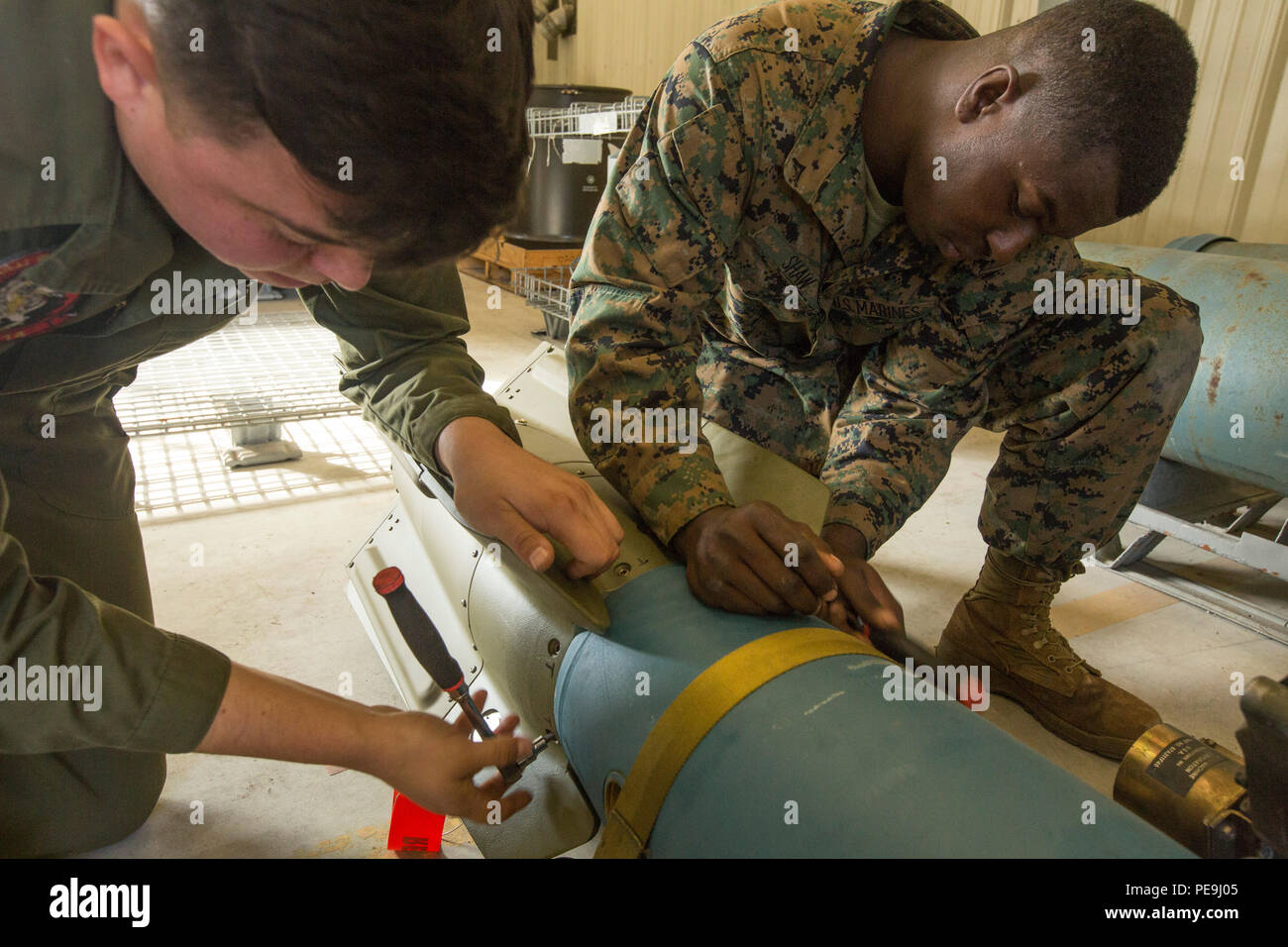 U.S. Marine Corps Lance Cpl. William H. Shaw, left, and Lance Cpl. Michaelalan Mills, aviation ordnance systems technicians assigned to Marine Aviation Logistics Squadron (MALS) 14, assemble a guided bomb unit on Marine Corps Air Station Cherry Point, N.C., Nov. 18, 2015. MALS-14 provides support to aviation units in 2nd Marine Aircraft Wing by preparing munitions and repairing weapon systems. (U.S. Marine Corps photo by Lance Cpl. Jered T. Stone/Released) - Stock Image
