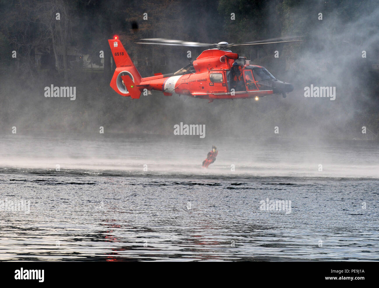 A U.S. Coast Guardsmen drops into waters during extraction training as part of the Disaster Management Exchange event on Joint Base Lewis-McChord, Wash., Nov. 20, 2015. The DME is a U.S. Pacific-hosted exchange focused on providing international humanitarian assistance and disaster relief to countries in the Indo-Pacific that could be affected by natural disasters. (Photos by Sgt. 1st Class Andrew Porch, 28th Public Affairs Detachment) - Stock Image