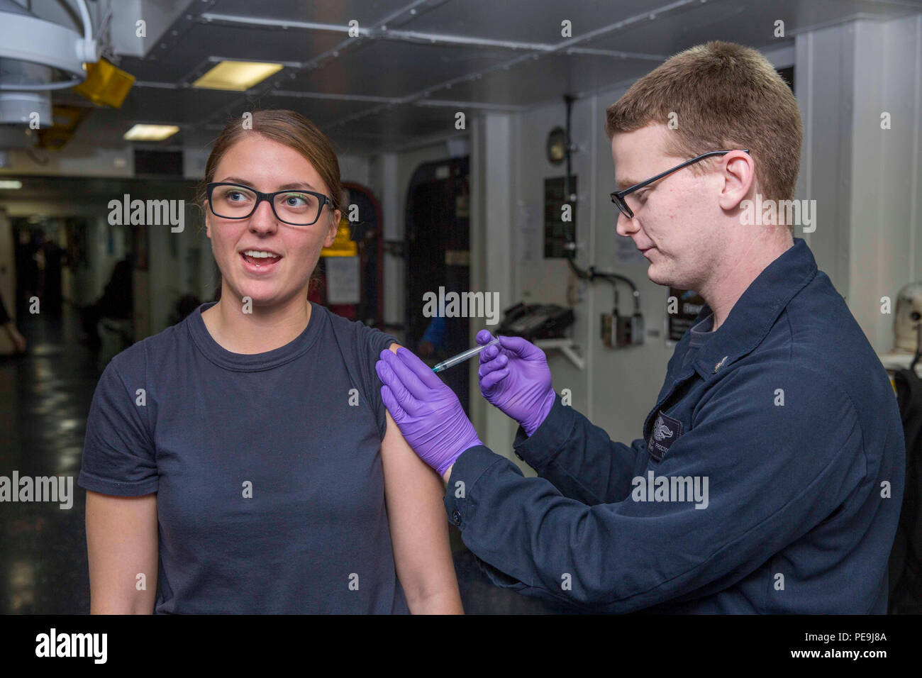 151120-N-XJ788-002 U.S. 5TH FLEET AREA OF OPERATIONS (Nov. 20, 2015) Hospital Corpsman 3rd Class Bradley Proctor, from Bossier City, La., administers an immunization shot to Intelligence Specialist 3rd Class Kaitlyn Smiddy, from Castle Rock, Colo., aboard the amphibious assault ship USS Kearsarge (LHD 3). Kearsarge is the flagship for the Kearsarge Amphibious Ready Group (ARG) and, with the embarked 26th Marine Expeditionary Unit (26 MEU), is deployed in support of maritime security operations and theater security cooperation efforts in the U.S. 5th Fleet area of operations. (U.S. Navy photo b - Stock Image