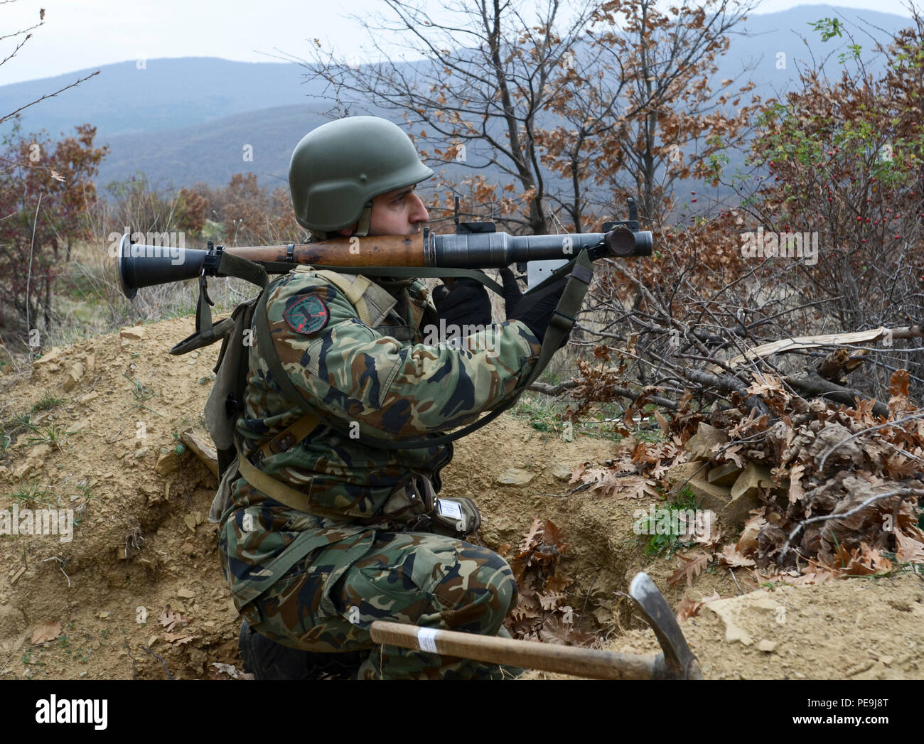 Bulgarian Army Pvt. Varban Durchev, of 1st Battalion, 61st Mechanized Brigade, suppresses the enemy with a Rocket-Propelled Grenade Launcher (RPG-7) during Exercise Peace Sentinel at Novo Selo Training Center, Bulgaria, Nov. 21, 2015. Durchev used a small pickaxe (foreground) to dig out an area in which he could position himself to fire the RPG-7 behind cover. (Photo by Staff Sgt. Steven M. Colvin/Released) - Stock Image