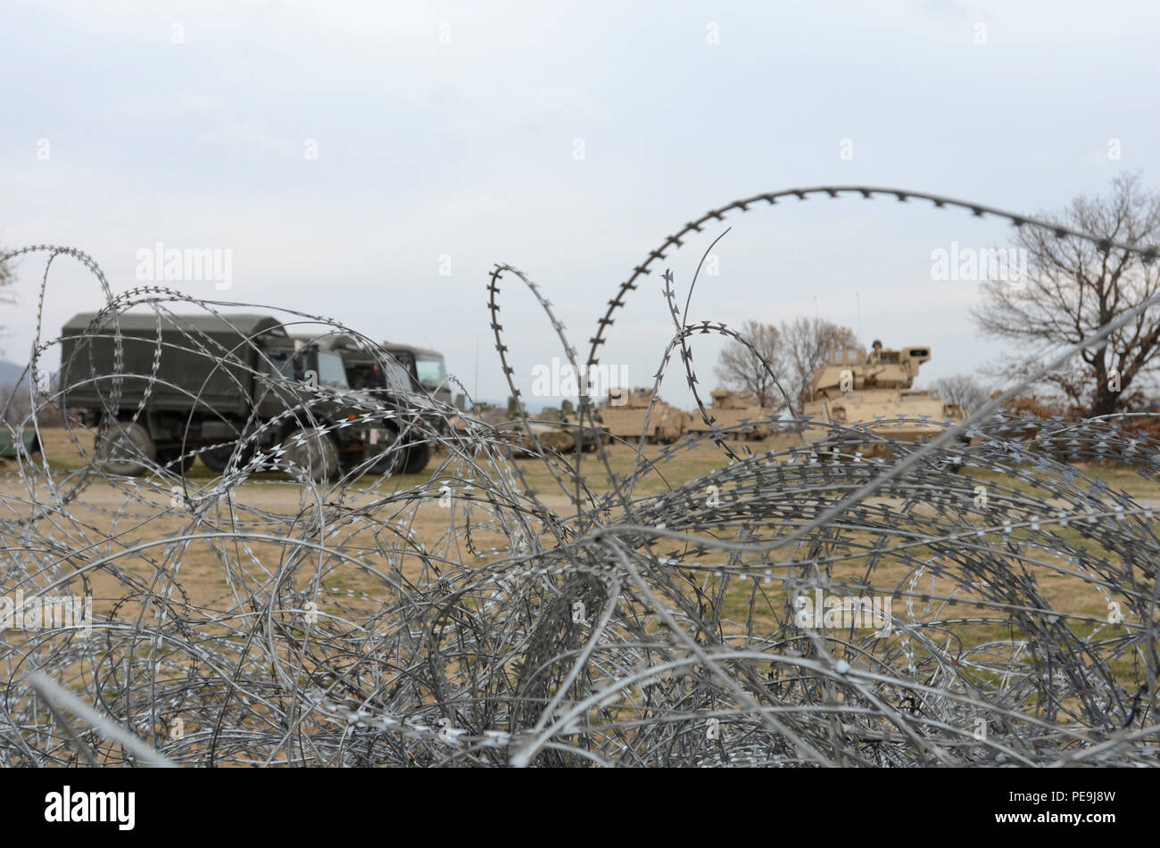 Bulgarian and U.S. Army vehicles park in the open field on the other side of the pile of tangled concertina wire (C-wire) during Exercise Peace Sentinel at Novo Selo Training Center, Bulgaria, Nov. 21, 2015. (Photo by Staff Sgt. Steven M. Colvin/Released) - Stock Image