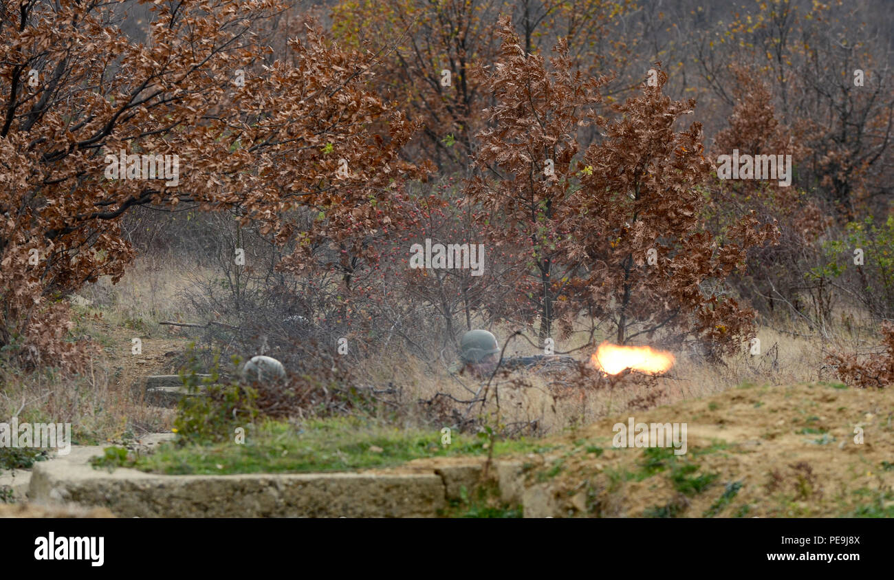 Bulgarian soldiers fire their weapons to suppress the enemy during Exercise Peace Sentinel at Novo Selo Training Center, Bulgaria, Nov. 21, 2015. (Photo by Staff Sgt. Steven M. Colvin/Released) - Stock Image