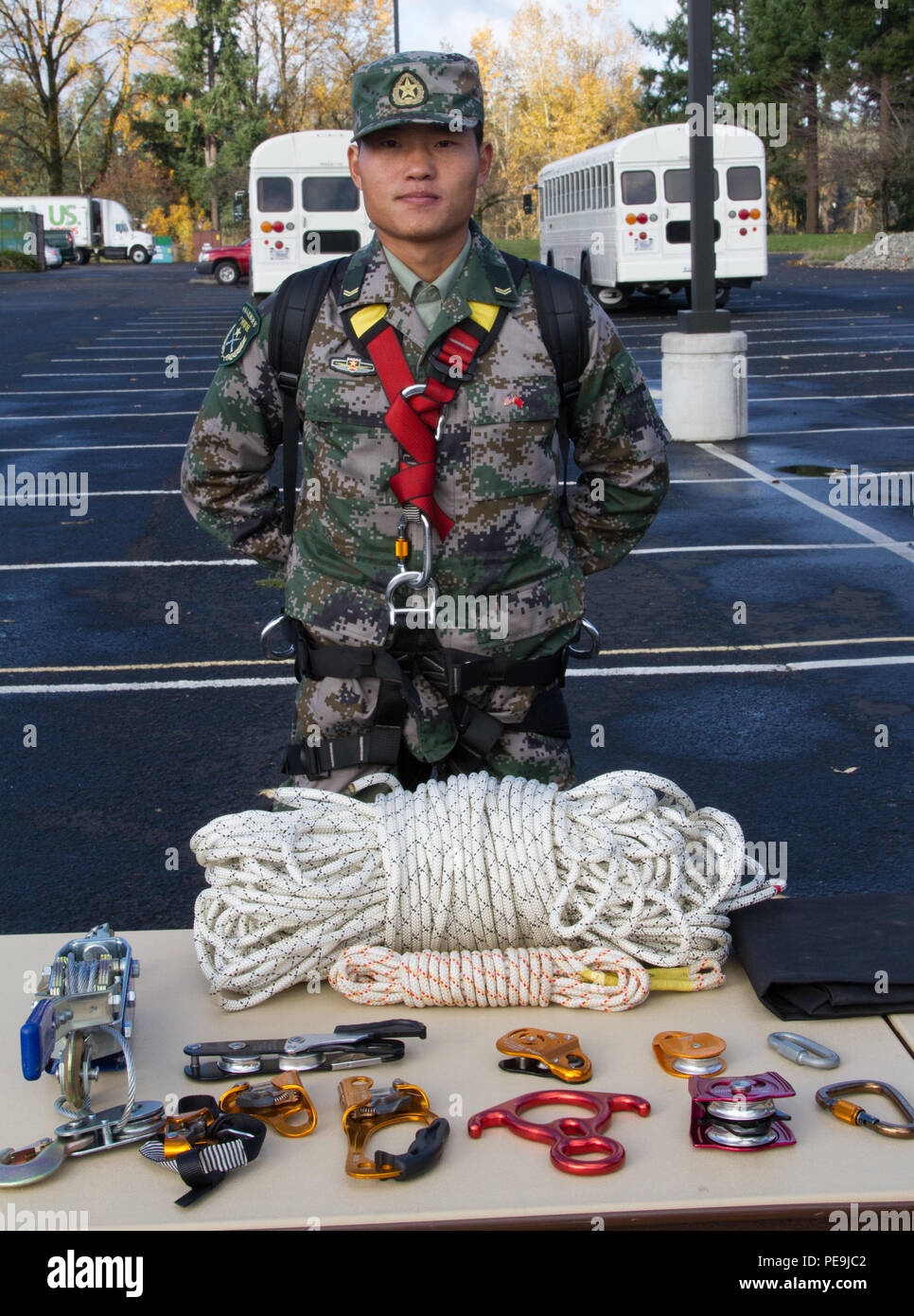 A Soldier with People's Republic of China People's Liberation Army displays rappelling equipment during the Disaster Management Exchange held at Joint Base Lewis McChord, Nov. 19, 2015. This is the 11th iteration of the DME, an annual U. S. Army Pacific- hosted exchange focused on humanitarian aide and disaster relief.  (U. S. Army photo by Staff Sgt. Trish McMurphy, 28th Public Affairs Detachment) - Stock Image