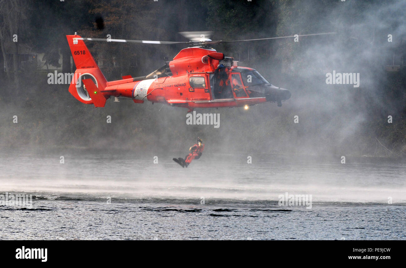 A U.S. Coast Guardsmen drops into waters during extraction training as part of the Disaster Management Exchange event on Joint Base Lewis-McChord, Wash., Nov. 20, 2015. The DME is a U.S. Pacific-hosted exchange focused on providing international humanitarian assistance and disaster relief to countries in the Indo-Pacific that could be affected by natural disasters - Stock Image