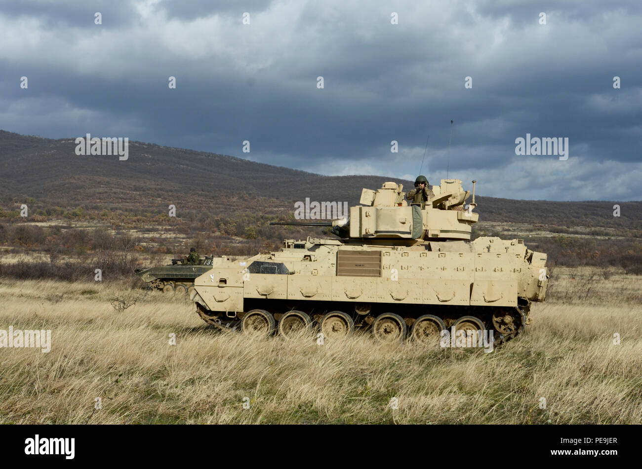 Bulgarian and U.S. soldiers make offensive movement on the enemy with a Boyevaya Mashina Pekhoty 1 (BMP -1P) and a Bradley Fighting Vehicle during Exercise Peace Sentinel at Novo Selo Training Center, Bulgaria, Nov. 22, 2015. (U.S. Army photo by Staff Sgt. Steven M. Colvin/Released) - Stock Image