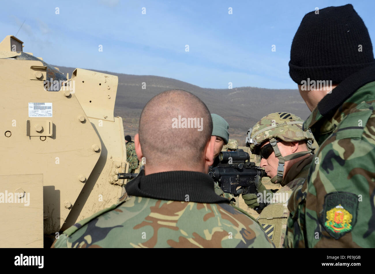 U.S. Army Sgt. Michael Conner of Apache Troop, 5th Squadron, 7th Cavalry Regiment, 3rd Infantry Division, Fort Stewart, Ga., shows some Bulgarian soldiers how to properly aim and fire a U.S. Army M4 carbine rifle during Exercise Peace Sentinel at Novo Selo Training Center, Bulgaria, Nov. 22, 2015. (U.S. Army photo by Staff Sgt. Steven M. Colvin/Released) - Stock Image