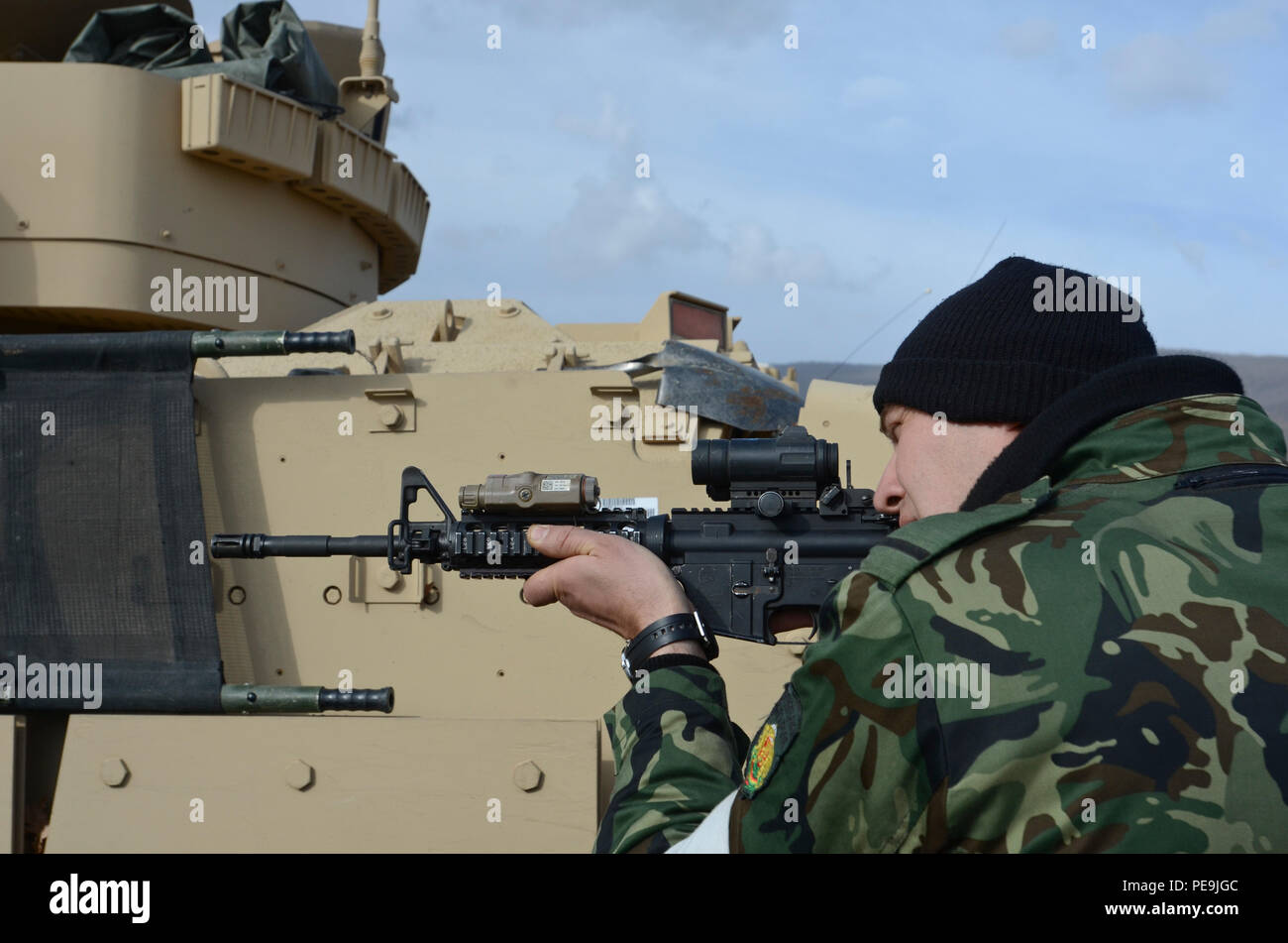 A Bulgarian soldier looks through an Advanced Combat Optical Gunsight (ACOG) during Exercise Peace Sentinel at Novo Selo Training Center, Bulgaria, Nov. 22, 2015. (U.S. Army photo by Staff Sgt. Steven M. Colvin/Released) - Stock Image