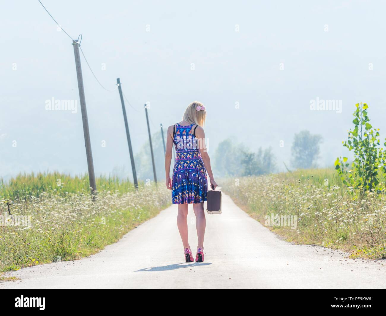 Sunlight mid-day 20s twenties attractive adult young woman outdoors by foot feet traveler traveling or run-away Stock Photo