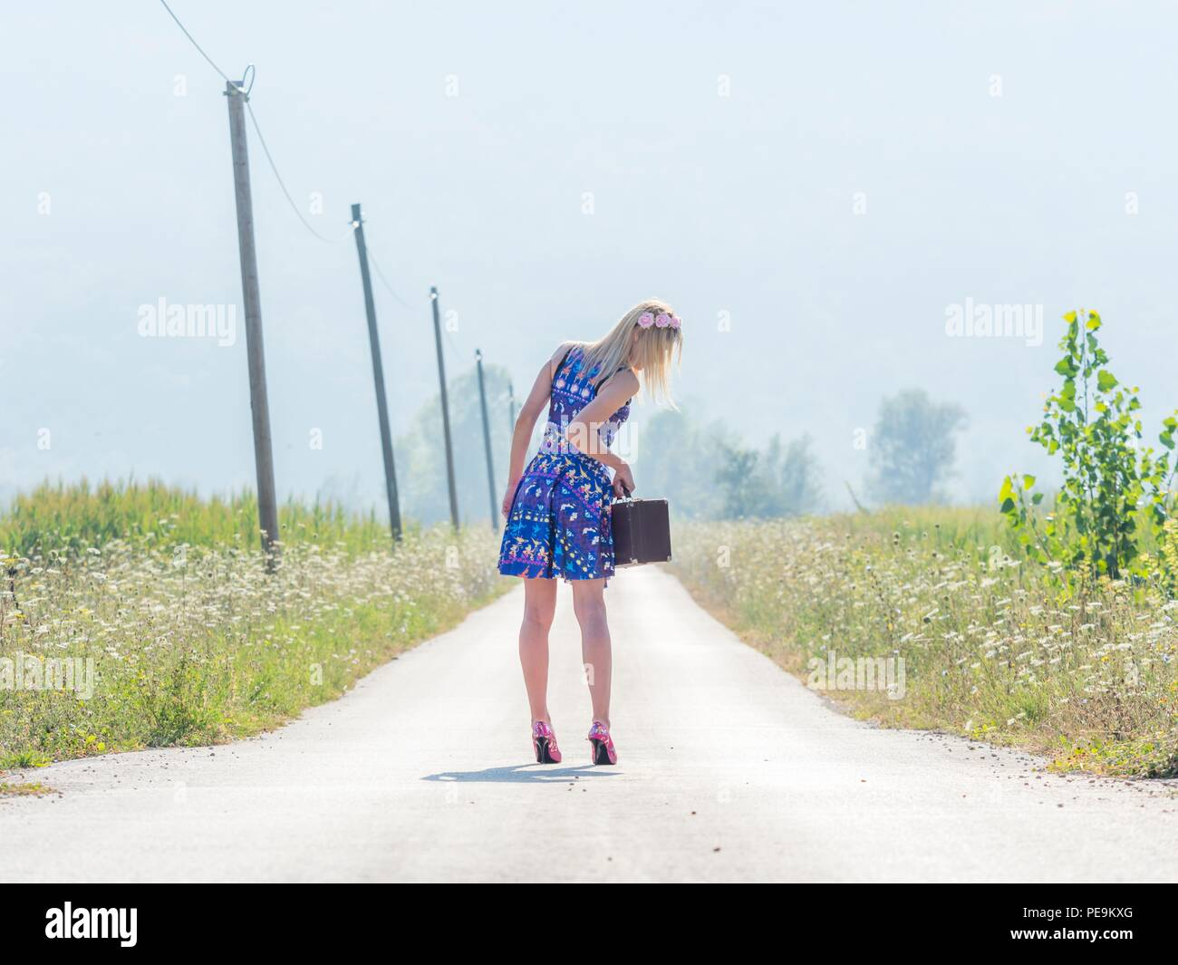 Sunlight mid-day 20s twenties attractive adult young woman outdoors by foot feet traveler traveling or run-away MR minidress clothing Stock Photo