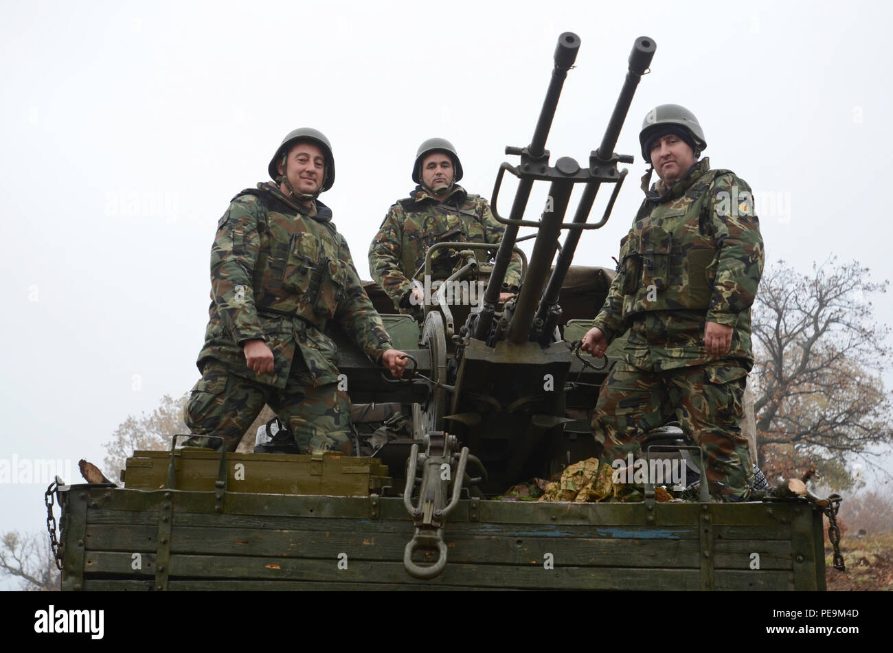 Bulgarian soldiers of 1-61st Mechanized Battalion pose for a picture on a ZU-23-2, which is a towed or improvised truck-mounted weapon that carries two 23 mm cannons for air defense, during Exercise Peace Sentinel at Novo Selo Training Center, Bulgaria, Nov. 24, 2015. (U.S. Army photo by Staff Sgt. Steven M. Colvin/Released) - Stock Image