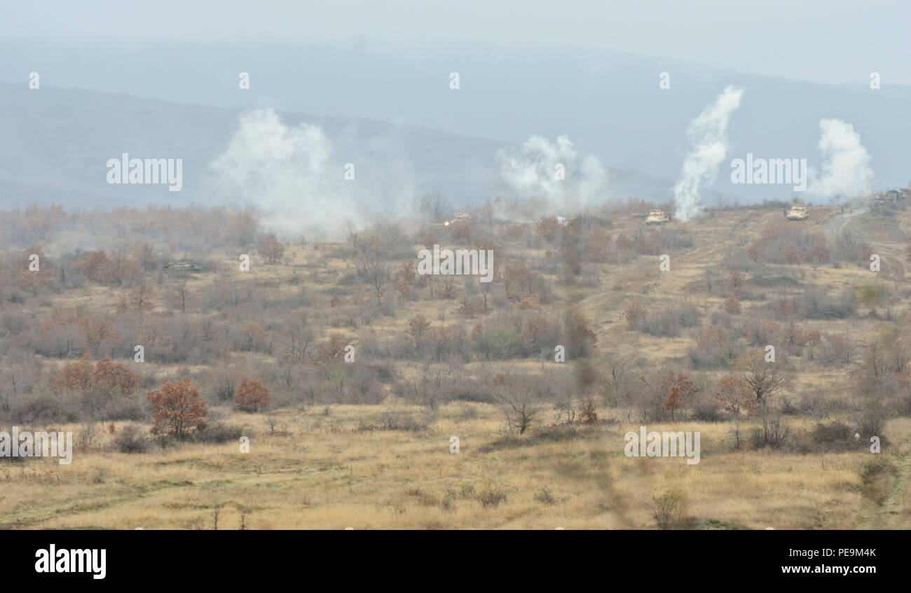 Smoke bombs are used to simulate exploded rounds as the enemy is on the approach during Exercise Peace Sentinel at Novo Selo Training Center, Bulgaria, Nov. 24, 2015. (U.S. Army photo by Staff Sgt. Steven M. Colvin/Released) - Stock Image