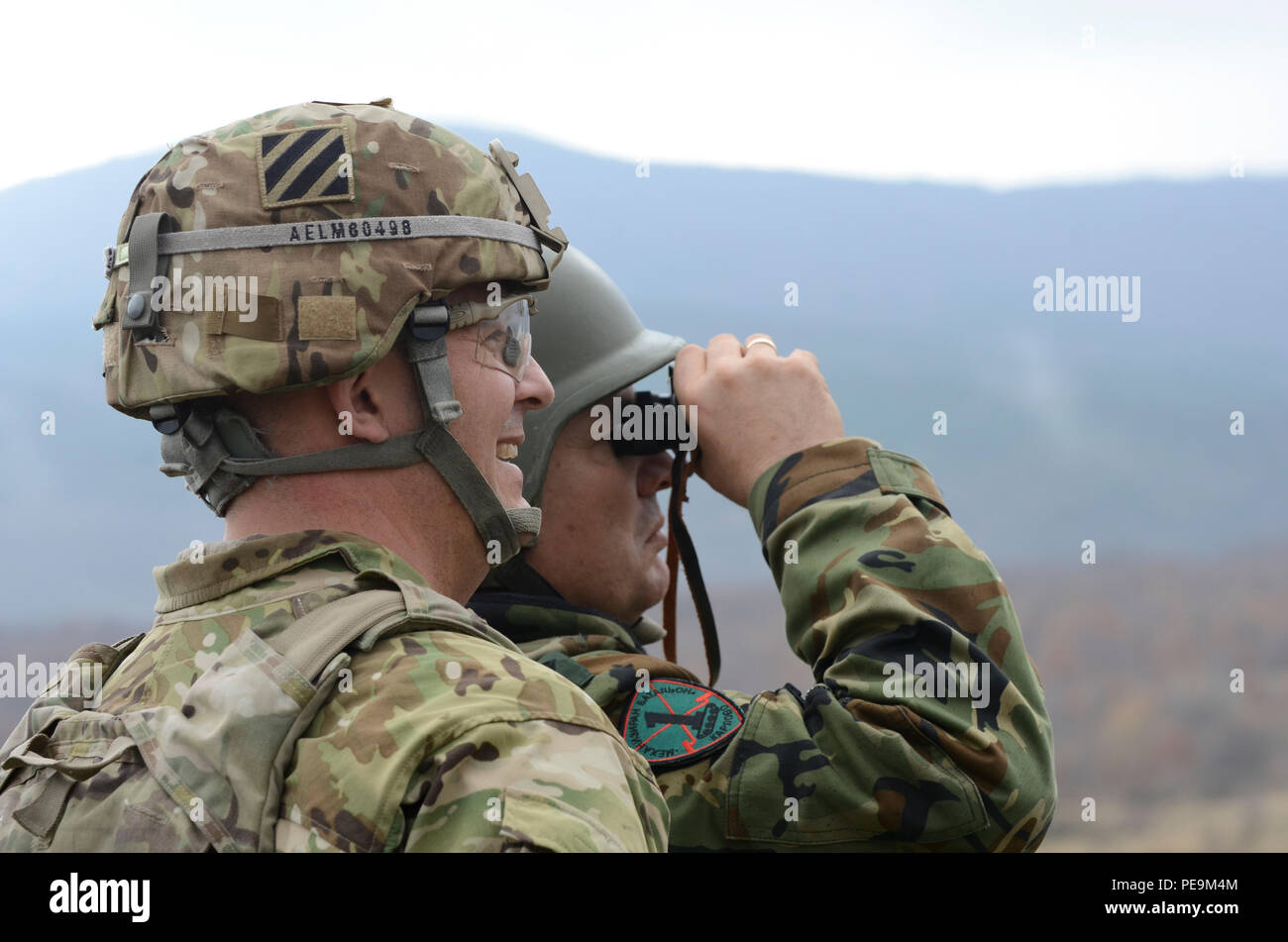 U.S. Army Lt. Col. Christopher S. Mahaffey, commander of 5th Squadron, 7th Cavalry Regiment, 3rd Infantry Division, stationed at Fort Stewart, Ga., and Bulgarian Army Lt. Col. Tzvetan, Kochankov, commander of 1-61st Mechanized Battalion, watch as U.S. and Bulgarian soldiers conduct tactical movements during Exercise Peace Sentinel at Novo Selo Training Center, Bulgaria, Nov. 24, 2015. (U.S. Army photo by Staff Sgt. Steven M. Colvin/Released) - Stock Image