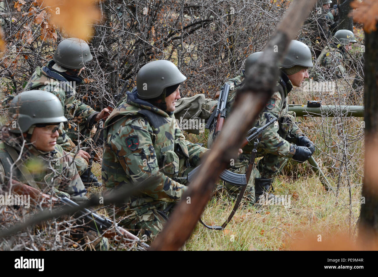 Bulgarian soldiers of 1-61st Mechanized Battalion steady their positions in the tree line as the enemy begins its approach during Exercise Peace Sentinel at Novo Selo Training Center, Bulgaria, Nov. 24, 2015. (U.S. Army photo by Staff Sgt. Steven M. Colvin/Released) - Stock Image