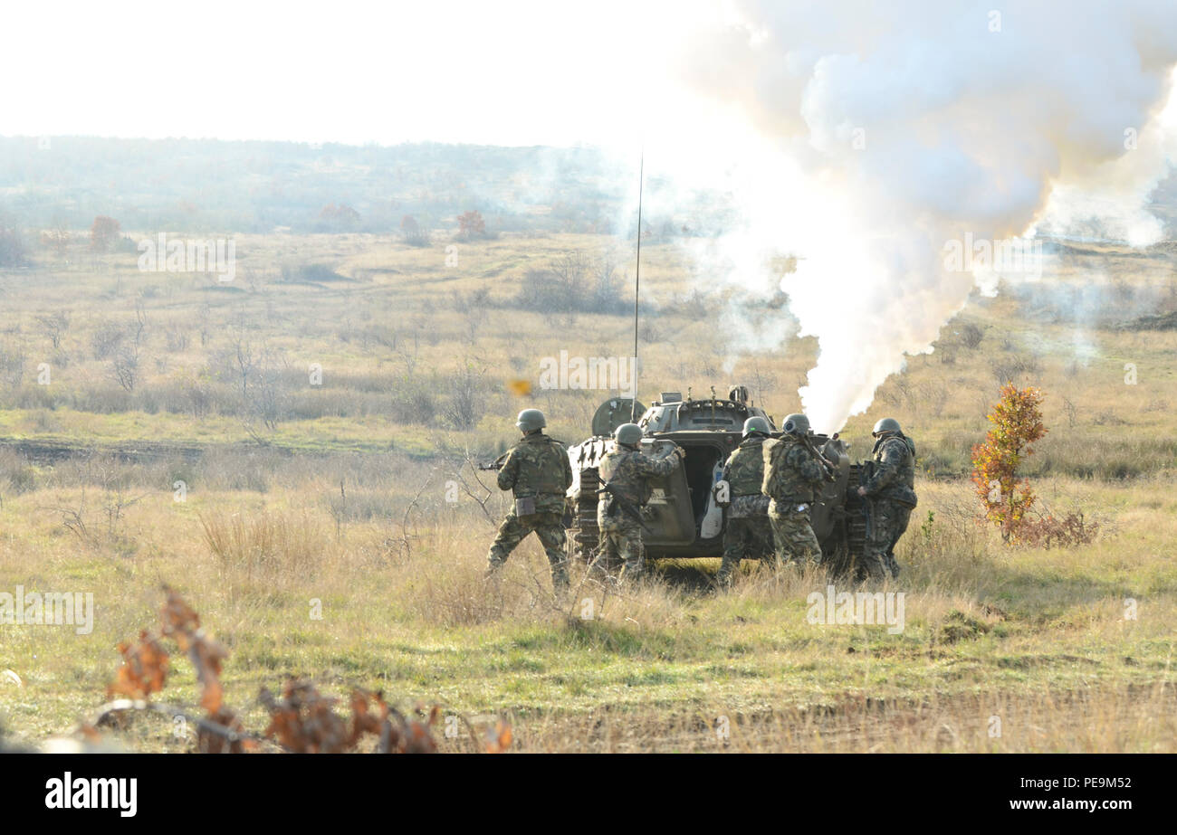 Bulgarian soldiers of 1-61st Mechanized Battalion dismount the Boyevaya Mashina Pekhoty 1 (BMP -1) as it disperses a massive amount of white smoke in order to conceal the soldiers as they begin their offensive approach on the enemy during Exercise Peace Sentinel at Novo Selo Training Center, Bulgaria, Nov. 24, 2015. (U.S. Army photo by Staff Sgt. Steven M. Colvin/Released) - Stock Image