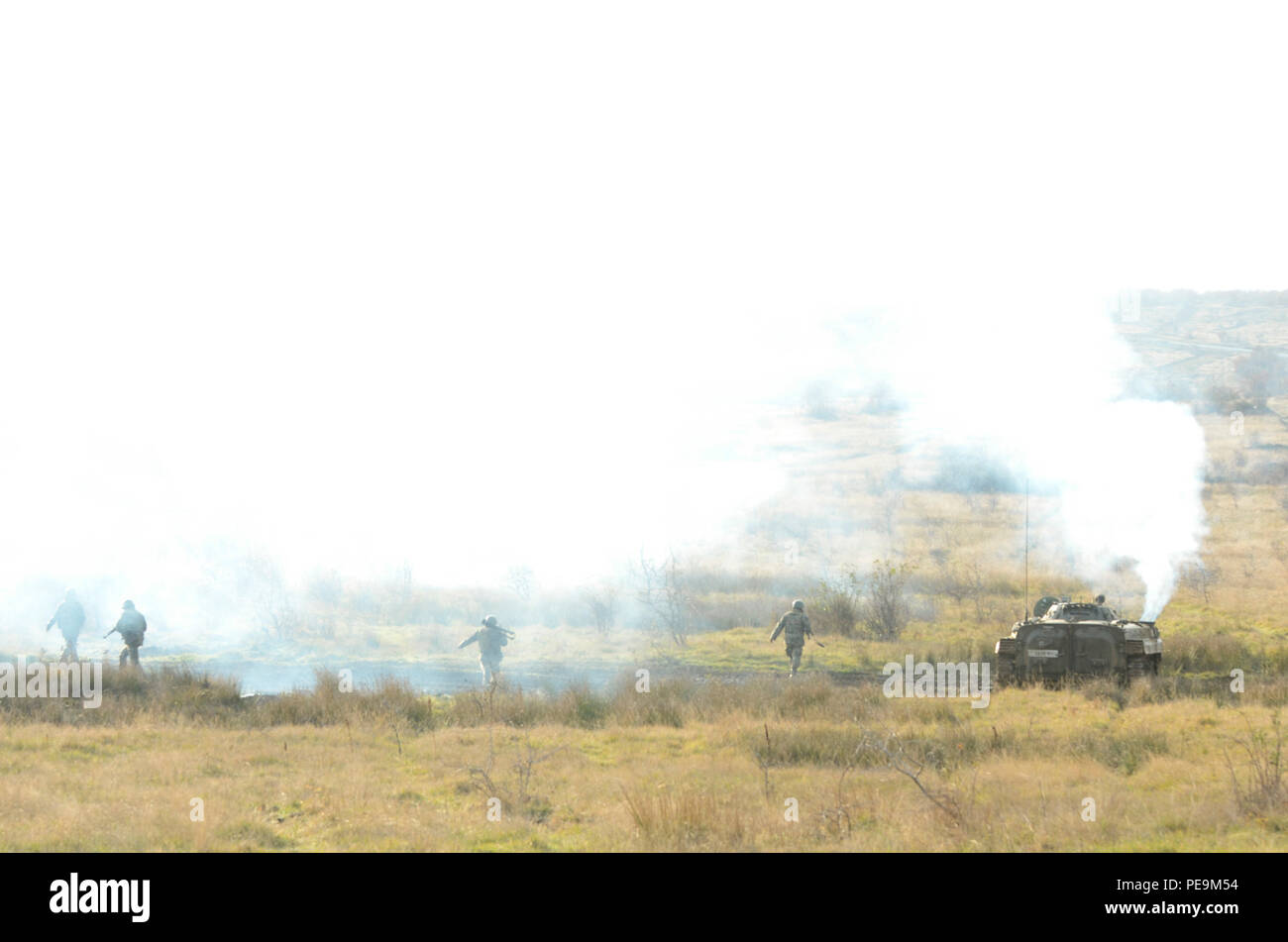 Bulgarian soldiers of 1-61st Mechanized Battalion begin their offensive approach on the enemy as the Boyevaya Mashina Pekhoty 1 (BMP -1) disperses a massive amount of white smoke in order to conceal the soldiers' movement during Exercise Peace Sentinel at Novo Selo Training Center, Bulgaria, Nov. 24, 2015. (U.S. Army photo by Staff Sgt. Steven M. Colvin/Released) - Stock Image