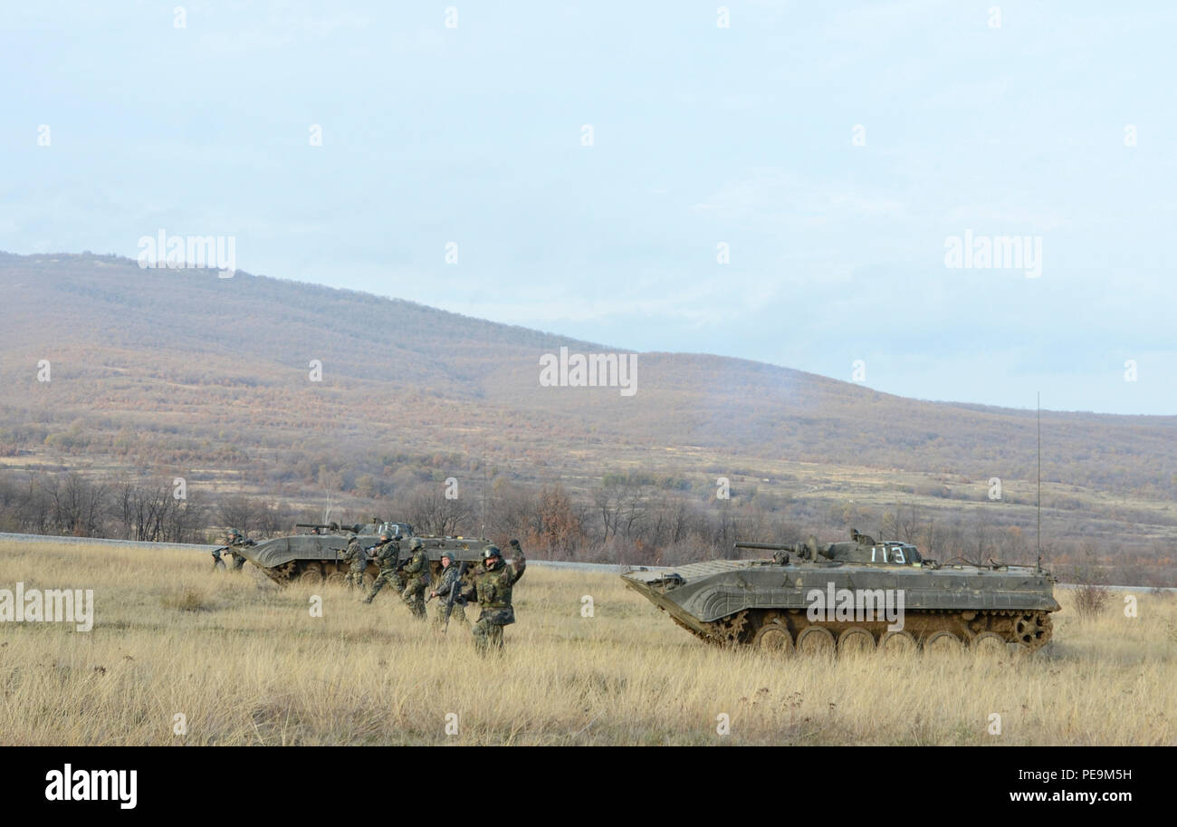 A Bulgarian team leader of 1-61st Mechanized Battalion signals to the other team leaders to stay on line as they continue their offensive approach on the enemy during Exercise Peace Sentinel at Novo Selo Training Center, Bulgaria, Nov. 24, 2015. (U.S. Army photo by Staff Sgt. Steven M. Colvin/Released) - Stock Image