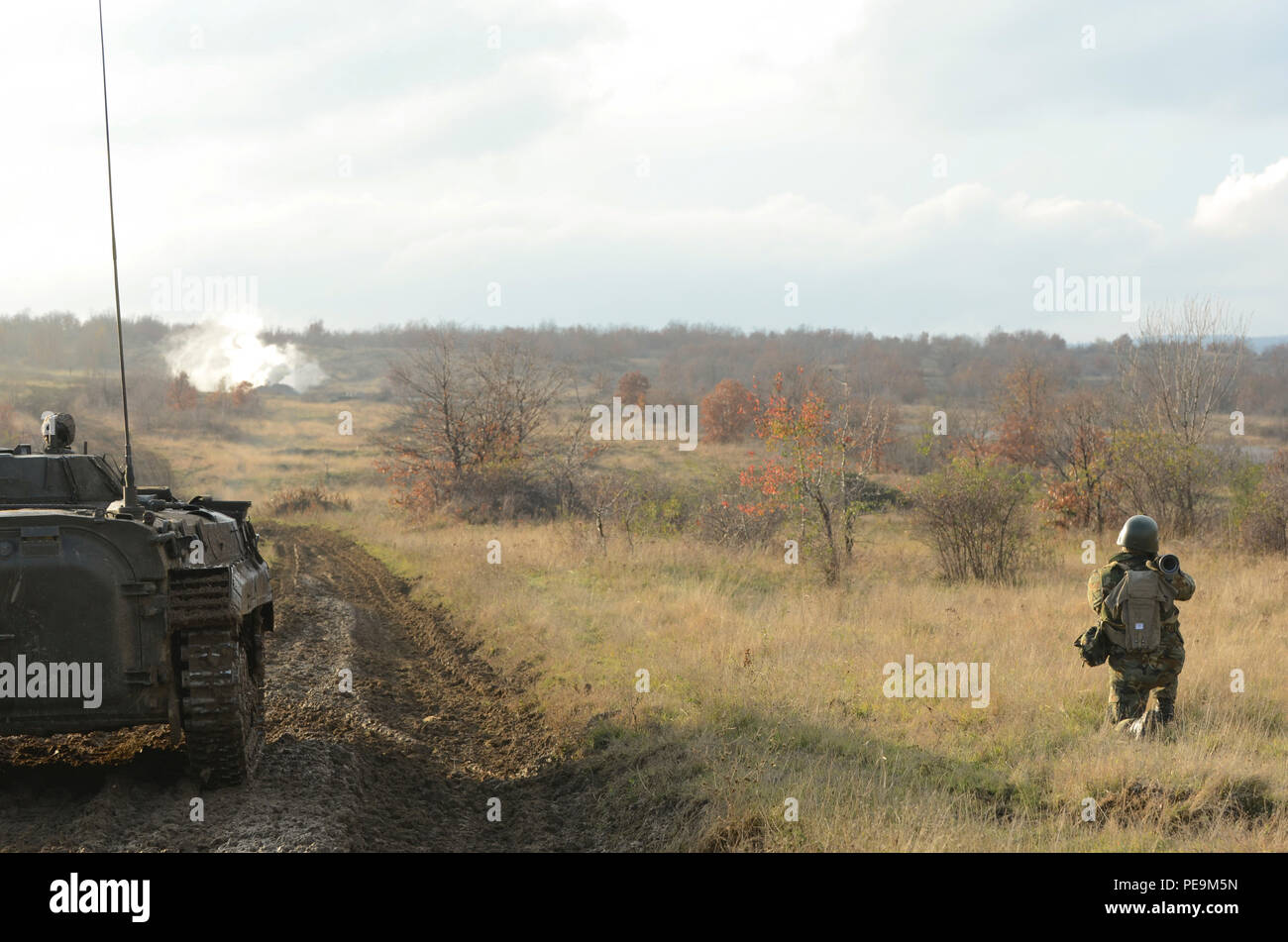 A Bulgarian soldier of 1-61st Mechanized Battalion kneels and pretends to fire a Rocket Propelled Grenade launcher as the smoke in the distance simulates an explosion during Exercise Peace Sentinel at Novo Selo Training Center, Bulgaria, Nov. 24, 2015. (U.S. Army photo by Staff Sgt. Steven M. Colvin/Released) - Stock Image