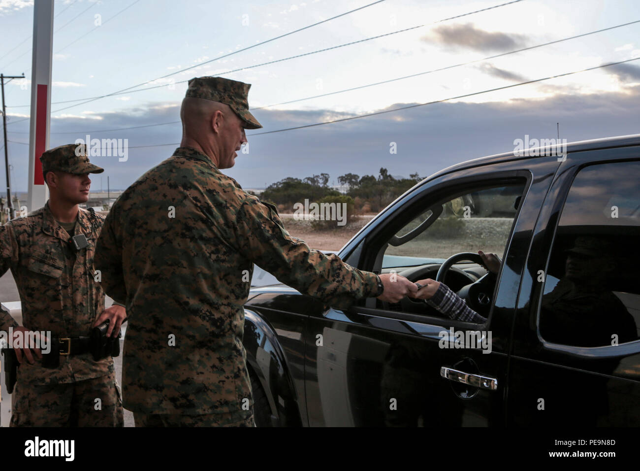 U.S. Marine Corps Sgt. Maj. Patrick Kimble, Sergeant Major, 3d Marine Aircraft Wing (3d MAW), greets a service member at an entry point of Marine Corps Air Station Miramar, San Diego, Calif., Nov. 25, 2015. Maj. Gen. Michael A Rocco, Commanding General, 3d MAW, Brig. Gen. Kevin Iiams, Assistant Wing Commander, 3d MAW, Sgt. Maj. Patrick Kimble, Sergeant Major, 3d MAW, and U.S. Navy Command Master Chief Petty Officer Frank Dominguez, Command Master Chief, 3d MAW, wished a happy holiday to service members and Department of Defense employees as they entered the base. (U.S. Marine Corps photo by Cp - Stock Image