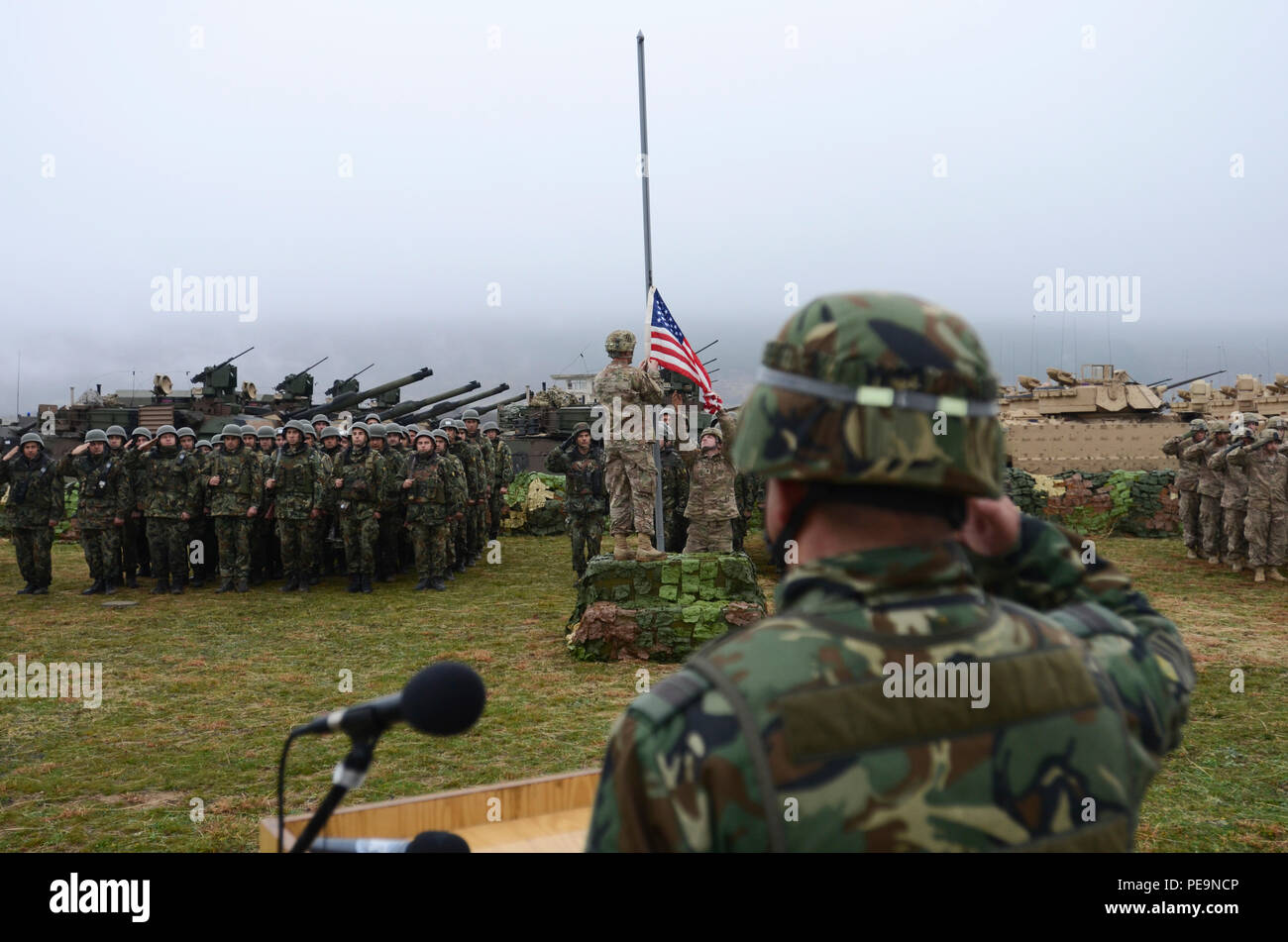 U.S. Soldiers of 5th Squadron, 7th Cavalry Regiment, 3rd Infantry Division, stationed at Fort Stewart, Ga., take the U.S. flag down representing the close of Exercise Peace Sentinel at Novo Selo Training Center, Bulgaria, Nov. 24, 2015. Peace Sentinel is a joint exercise that focuses on interoperability between the Bulgarian and U.S. forces. (U.S. Army photo by Staff Sgt. Steven M. Colvin/Released) - Stock Image