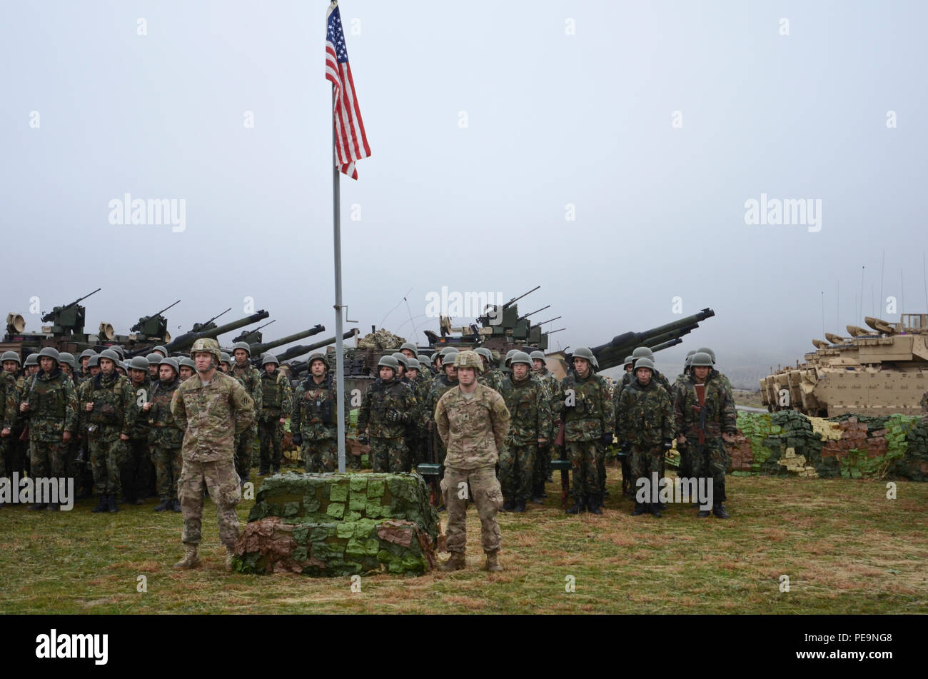 U.S. Soldiers of 5th Squadron, 7th Cavalry Regiment, 3rd Infantry Division, stationed at Fort Stewart, Ga., stand at parade rest at the base of the flag pole as Bulgarian soldiers stand in formation behind them during the closing ceremony of Exercise Peace Sentinel at Novo Selo Training Center, Bulgaria, Nov. 24, 2015. (U.S. Army photo by Staff Sgt. Steven M. Colvin/Released) - Stock Image
