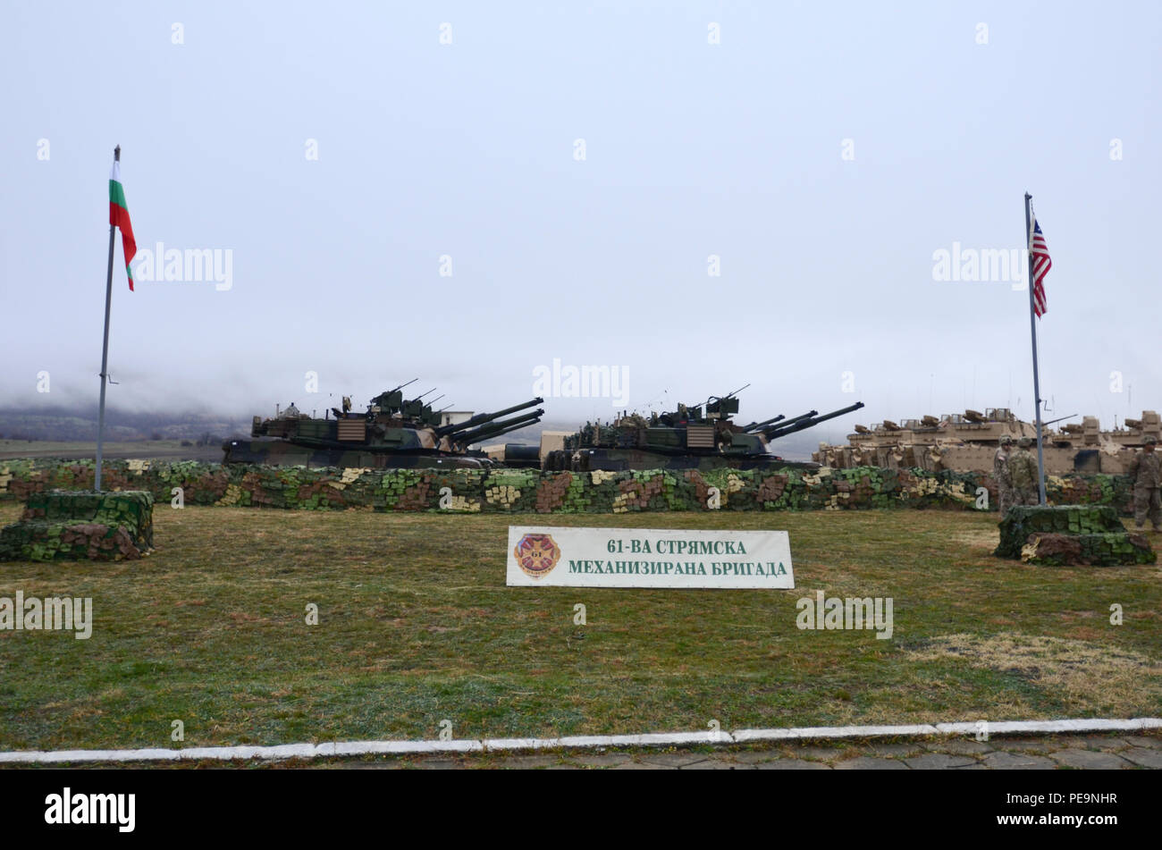 U.S. Army M1A2 System Enhancement Package Version 2 Abrams tanks and Bradley Fighting Vehicles are in formation behind the Bulgarian and U.S. flags during the closing ceremony of Exercise Peace Sentinel at Novo Selo Training Center, Bulgaria, Nov. 24, 2015. (U.S. Army photo by Staff Sgt. Steven M. Colvin/Released) - Stock Image