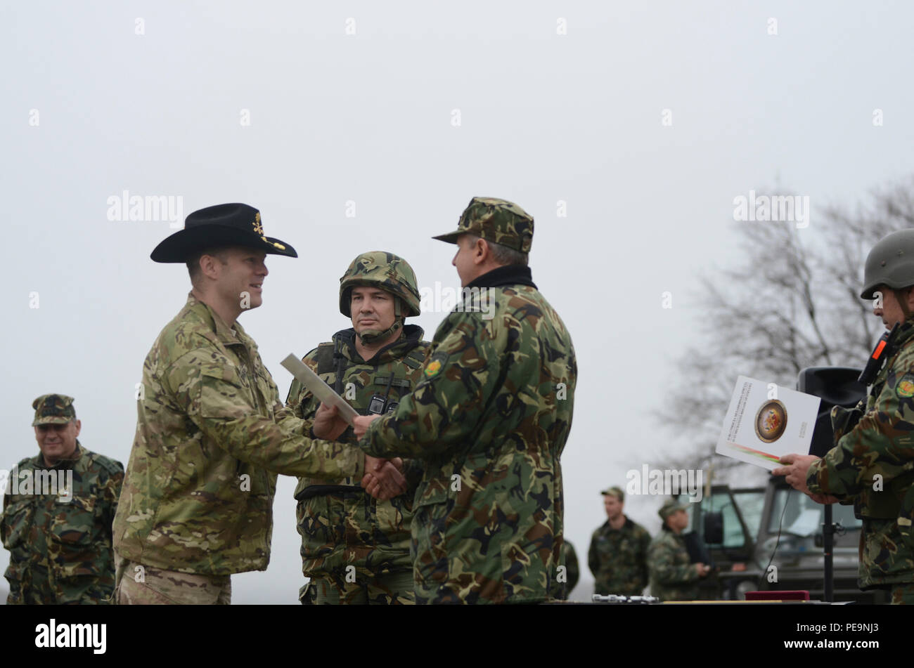 Bulgarian Col. Margarit Mihailov (right), the commander of 61st Mechanized Brigade, presents U.S. Army Maj. Brennan Speakes, the operations officer in charge of 5th Squadron, 7th Cavalry Regiment, stationed at Fort Stewart, Ga., with a certificate of appreciation during the closing ceremony of Exercise Peace Sentinel at Novo Selo Training Center, Bulgaria, Nov. 24, 2015. (U.S. Army photo by Staff Sgt. Steven M. Colvin/Released) - Stock Image