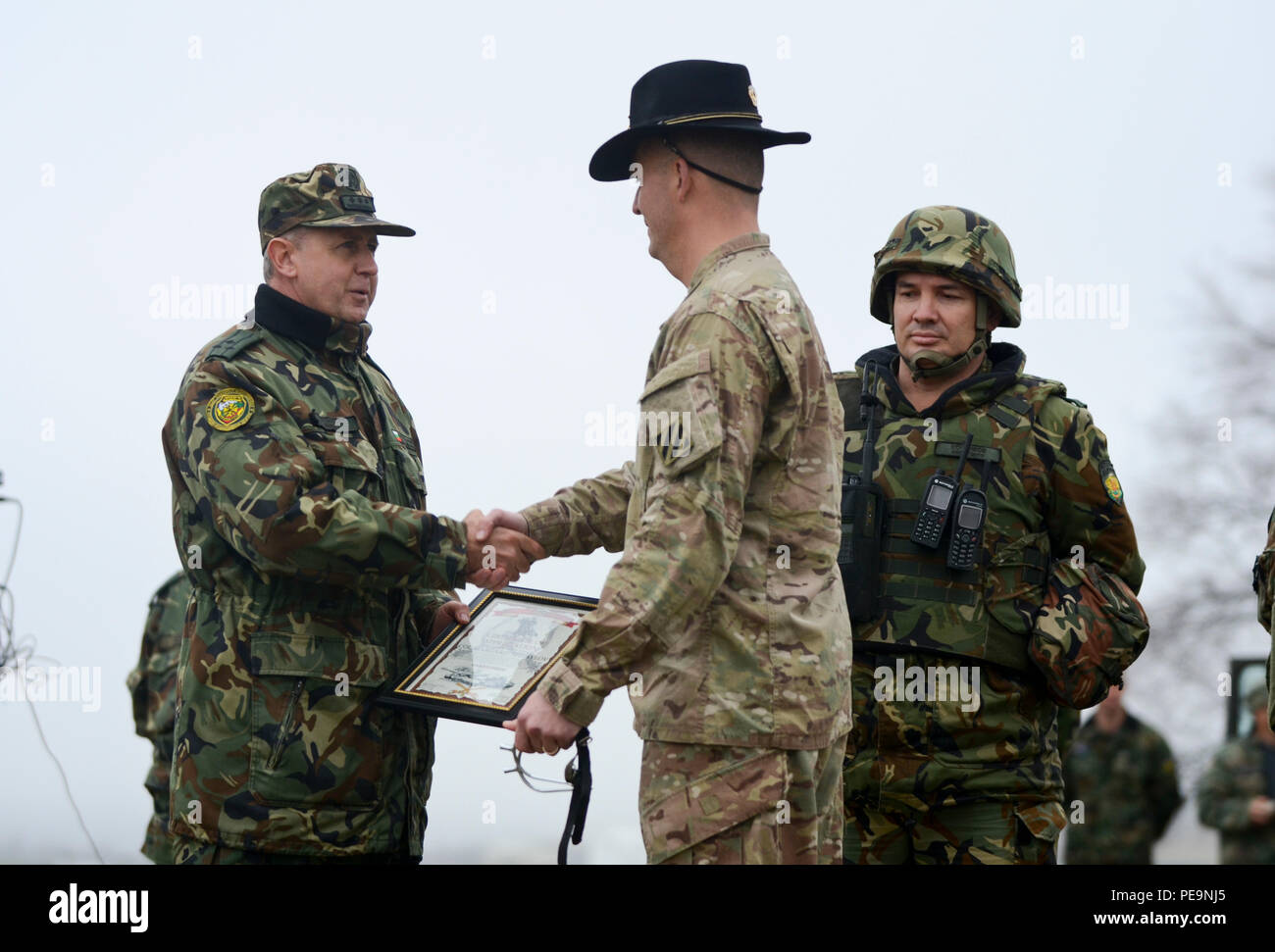 U.S. Army Lt. Col. Christopher Mahaffey (center), the commander of 5th Squadron, 7th Cavalry Regiment, 3rd Infantry Division, stationed at Fort Stewart, Ga., shakes hands with and presents gifts to Bulgarian Col. Margarit Mihailov (left), the commander of 61st Mechanized Brigade, during the closing ceremony of Exercise Peace Sentinel at Novo Selo Training Center, Bulgaria, Nov. 24, 2015. (U.S. Army photo by Staff Sgt. Steven M. Colvin/Released) - Stock Image