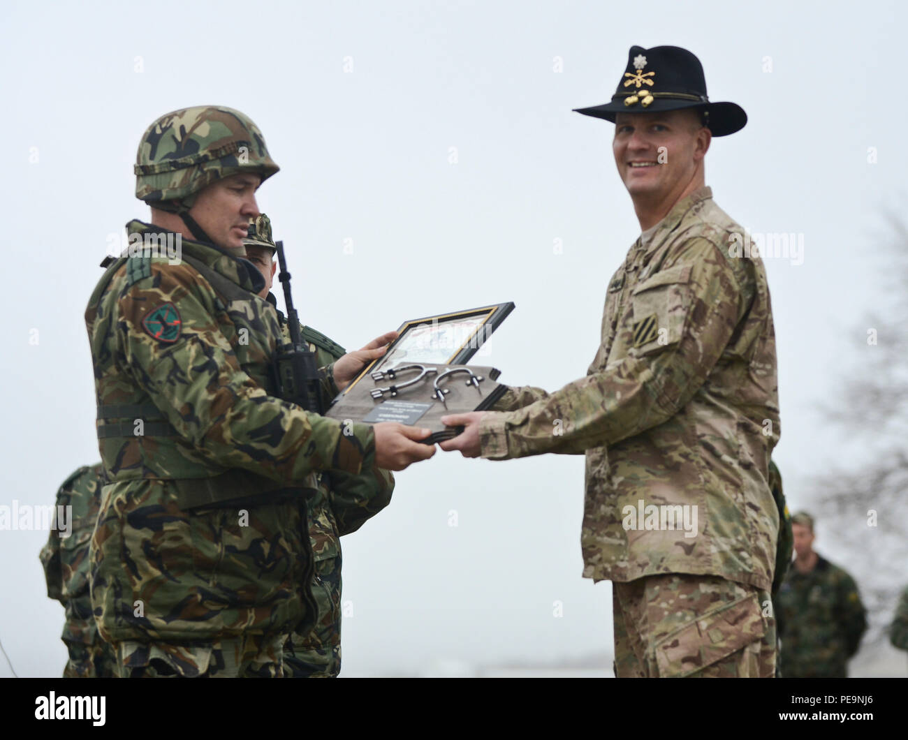 U.S. Army Lt. Col. Christopher Mahaffey (right), commander of 5th Squadron, 7th Cavalry Regiment, 3rd Infantry Division, stationed at Fort Stewart, Ga., presents gifts to Bulgarian Lt. Col. Tzvetan Kochankov (left), the commander of 1-61st Mechanized Battalion, during the closing ceremony of Exercise Peace Sentinel at Novo Selo Training Center, Bulgaria, Nov. 24, 2015. (U.S. Army photo by Staff Sgt. Steven M. Colvin/Released) - Stock Image