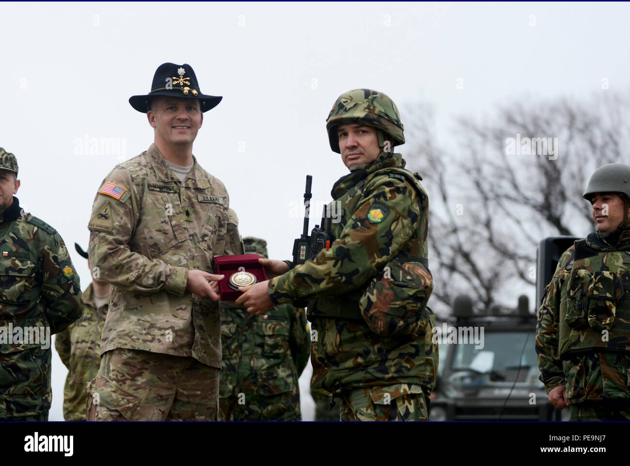 Bulgarian Lt. Col. Tzvetan Kochankov (right), the commander of 1-61st Mechanized Battalion, presents a gift to U.S. Army Lt. Col. Christopher Mahaffey (left), the commander of 5th Squadron, 7th Cavalry Regiment, 3rd Infantry Division, stationed at Fort Stewart, Ga., during the closing ceremony of Exercise Peace Sentinel at Novo Selo Training Center, Bulgaria, Nov. 24, 2015. (U.S. Army photo by Staff Sgt. Steven M. Colvin/Released) - Stock Image