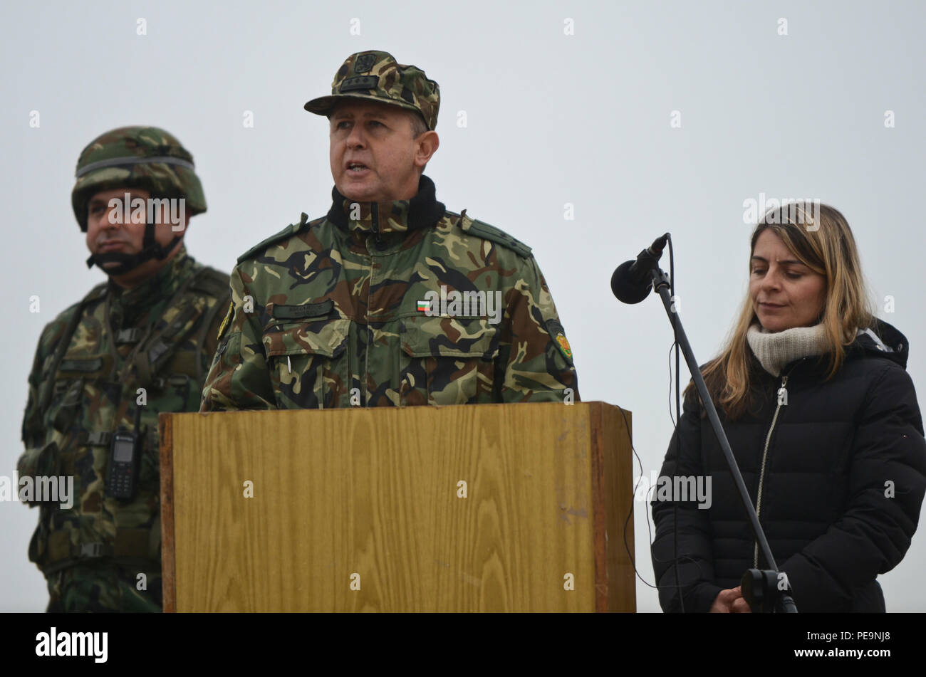 Bulgarian Col. Margarit Mihailov (center), the commander of 61st Mechanized Brigade, gives the closing comments during the closing ceremony of Exercise Peace Sentinel at Novo Selo Training Center, Bulgaria, Nov. 24, 2015. Kristina Brunson (right), a linguist, interprets the Bulgarian language into English. (U.S. Army photo by Staff Sgt. Steven M. Colvin/Released) - Stock Image