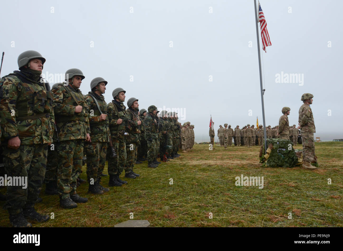 U.S. Soldiers of 5th Squadron, 7th Cavalry Regiment, 3rd Infantry Division, stationed at Fort Stewart, Ga., stand at parade rest at the base of flag pole as U.S. and Bulgarian Soldiers of 61st Mechanized Brigade stand in formation during the closing ceremony of Exercise Peace Sentinel at Novo Selo Training Center, Bulgaria, Nov. 24, 2015. (U.S. Army photo by Staff Sgt. Steven M. Colvin/Released) - Stock Image