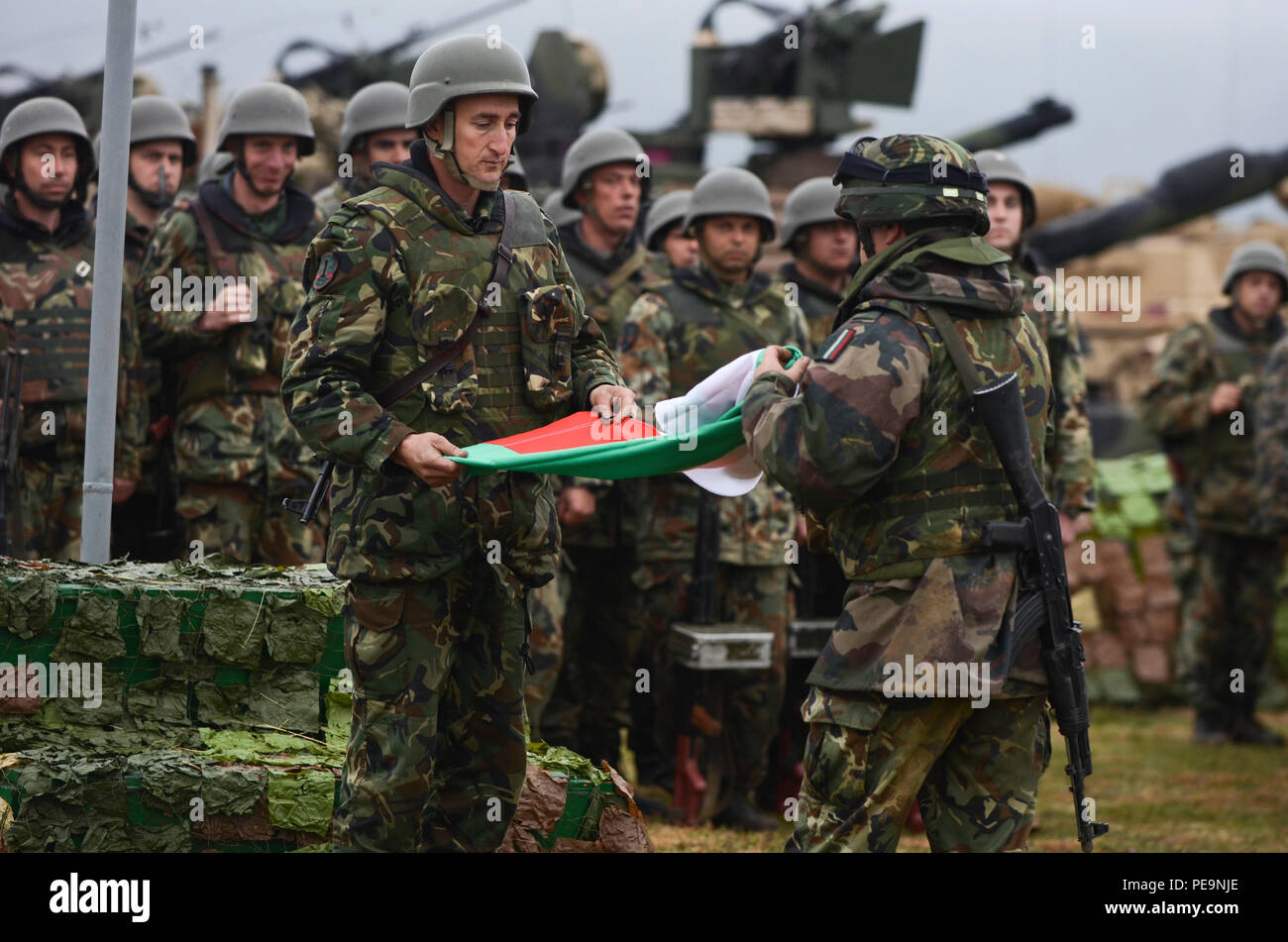 Bulgarian soldiers of 61st Mechanized Brigade fold the Bulgarian flag during the closing ceremony of Exercise Peace Sentinel at Novo Selo Training Center, Bulgaria, Nov. 24, 2015. (U.S. Army photo by Staff Sgt. Steven M. Colvin/Released) - Stock Image