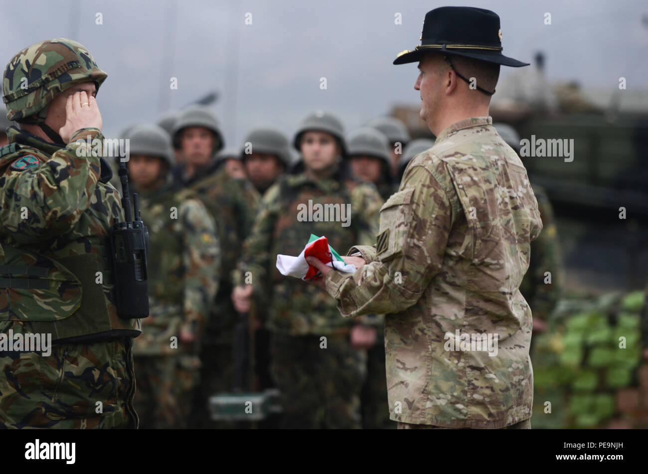 Bulgarian Lt. Col. Tzvetan Kochankov (left), commander of 1-61st Mechanized Battalion, salutes after handing off the Bulgarian flag to U.S. Army Lt. Col. Christopher Mahaffey (right), the commander of 5th Squadron, 7th Cavalry Regiment, 3rd Infantry Division, stationed at Fort Stewart, Ga., during the closing ceremony of Exercise Peace Sentinel at Novo Selo Training Center, Bulgaria, Nov. 24, 2015. (U.S. Army photo by Staff Sgt. Steven M. Colvin/Released) - Stock Image