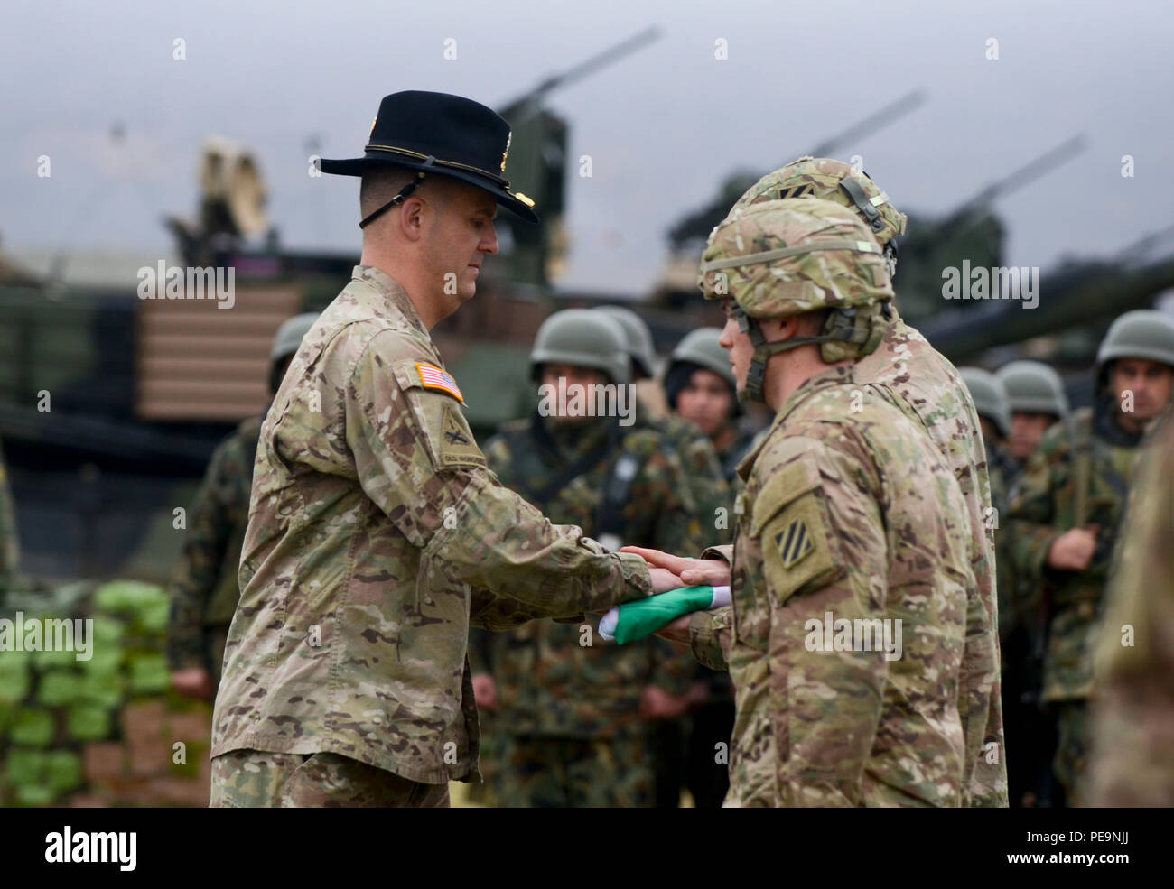 U.S. Army Lt. Col. Christopher Mahaffey (left), the commander of 5th Squadron, 7th Cavalry Regiment, 3rd Infantry Division, stationed at Fort Stewart, Ga., hands the Bulgarian flag to the U.S. Soldiers during the closing ceremony of Exercise Peace Sentinel at Novo Selo Training Center, Bulgaria, Nov. 24, 2015. (U.S. Army photo by Staff Sgt. Steven M. Colvin/Released) - Stock Image