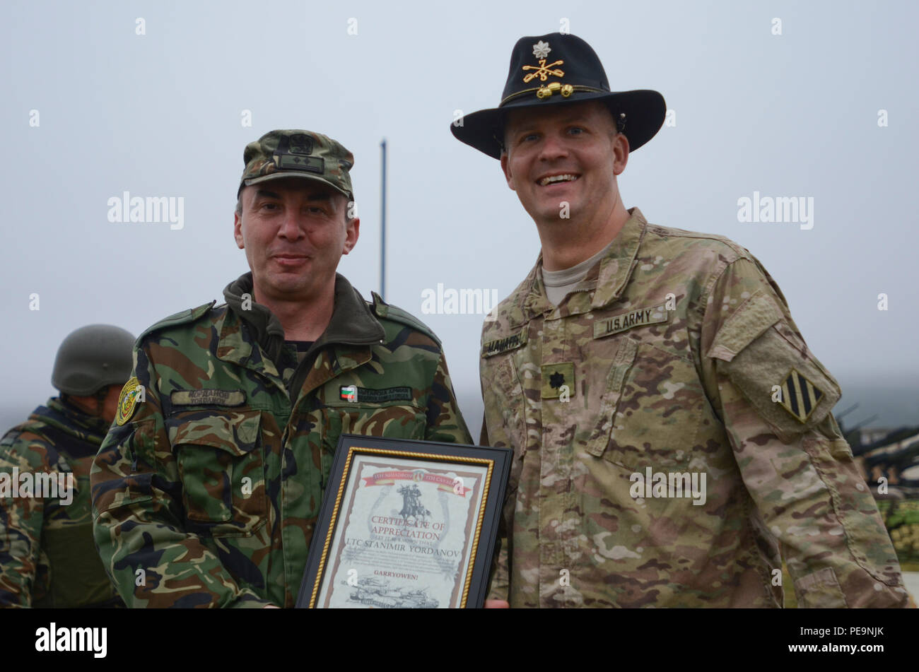 U.S. Army Lt. Col. Christopher Mahaffey (right), the commander of 5th Squadron, 7th Cavalry Regiment, 3rd Infantry Division, stationed at Fort Stewart, Ga., presents Bulgarian Lt. Col. Stanimir Yordanov (left), of 61st Mechanized Brigade, a certificate of appreciation during the closing ceremony of Exercise Peace Sentinel at Novo Selo Training Center, Bulgaria, Nov. 24, 2015. (U.S. Army photo by Staff Sgt. Steven M. Colvin/Released) - Stock Image