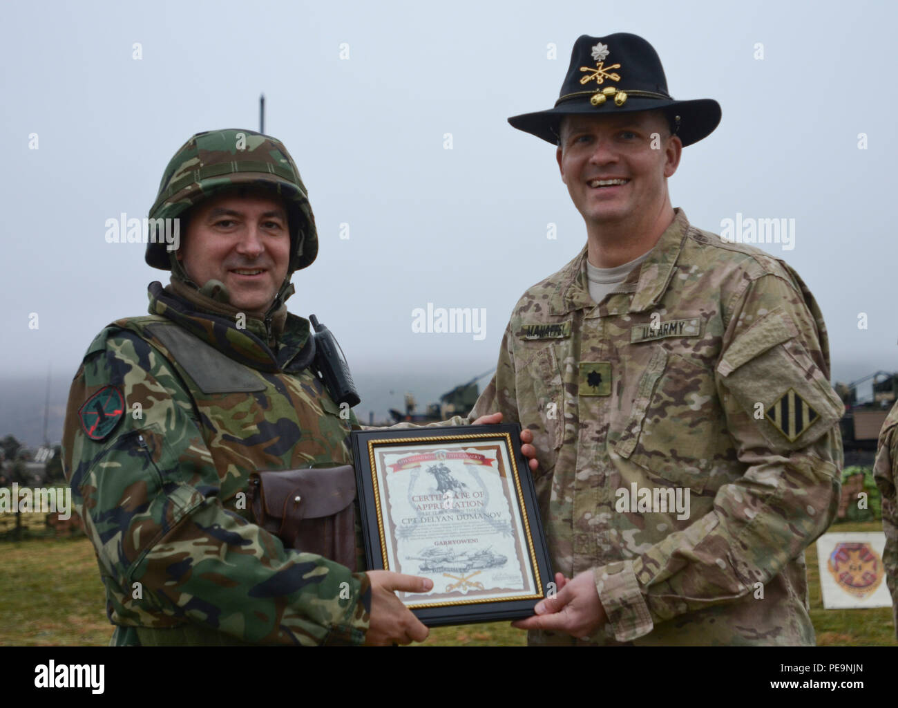 U.S. Army Lt. Col. Christopher Mahaffey (right), the commander of 5th Squadron, 7th Cavalry Regiment, 3rd Infantry Division, stationed at Fort Stewart, Ga., presents Bulgarian Capt. Delyan Dumanov (left), of 61st Mechanized Brigade, a certificate of appreciation during the closing ceremony of Exercise Peace Sentinel at Novo Selo Training Center, Bulgaria, Nov. 24, 2015. (U.S. Army photo by Staff Sgt. Steven M. Colvin/Released) - Stock Image