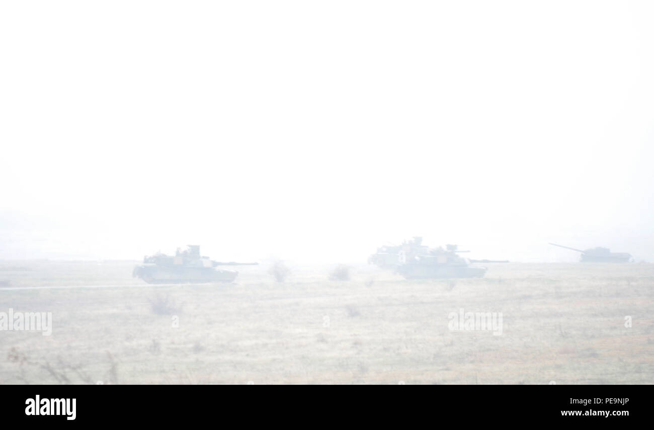 Through the fog and the rain, U.S. Soldiers of 5th Squadron, 7th Cavalry Regiment, 3rd Infantry Division, stationed at Fort Stewart, Ga., drive M1A2 System Enhancement Package Version 2 Abrams tanks toward the enemy during Exercise Peace Sentinel at Novo Selo Training Center, Bulgaria, Nov. 24, 2015. Peace Sentinel is a joint exercise that focuses on interoperability between the Bulgarian and U.S. forces. (U.S. Army photo by Staff Sgt. Steven M. Colvin/Released) - Stock Image