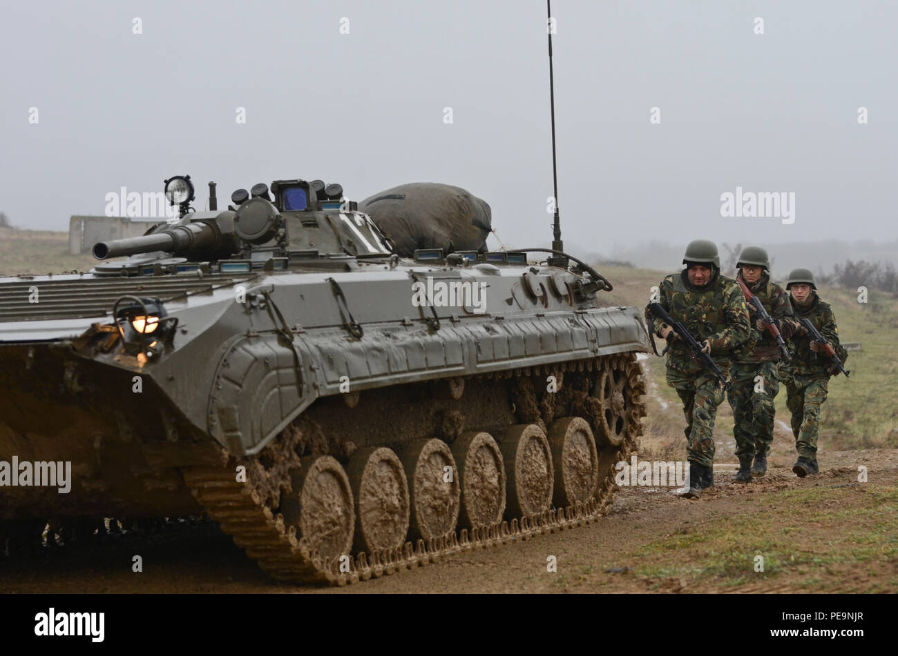 Bulgarian Soldiers of 1-61st Mechanized Battalion follow a Boyevaya Mashina Pekhoty 1 (BMP -1) through the muddy road during Exercise Peace Sentinel at Novo Selo Training Center, Bulgaria, Nov. 24, 2015. (U.S. Army photo by Staff Sgt. Steven M. Colvin/Released) - Stock Image