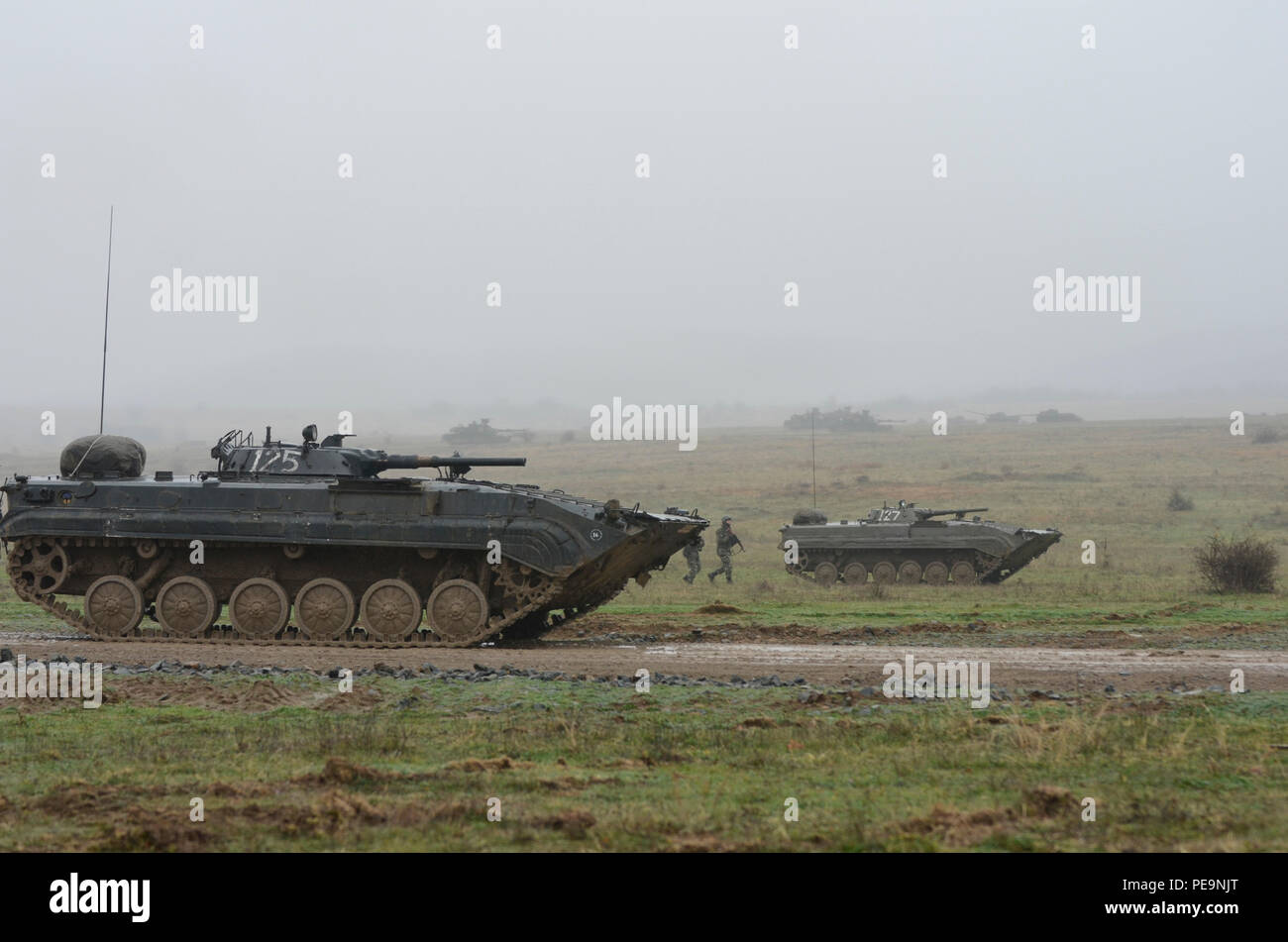 Bulgarian soldiers of 1-61st Mechanized Battalion follow along the side of Boyevaya Mashina Pekhoty 1's (BMP -1) through the wet and muddy terrain during Exercise Peace Sentinel at Novo Selo Training Center, Bulgaria, Nov. 24, 2015. (U.S. Army photo by Staff Sgt. Steven M. Colvin/Released) - Stock Image