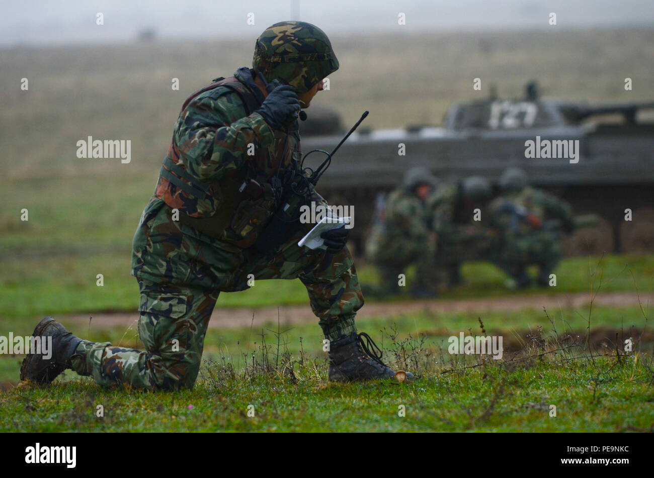 A Bulgarian soldier of 1-61st Mechanized Battalion communicates with other team leaders to make the next attack move on the enemy during Exercise Peace Sentinel at Novo Selo Training Center, Bulgaria, Nov. 24, 2015. (U.S. Army photo by Staff Sgt. Steven M. Colvin/Released) - Stock Image