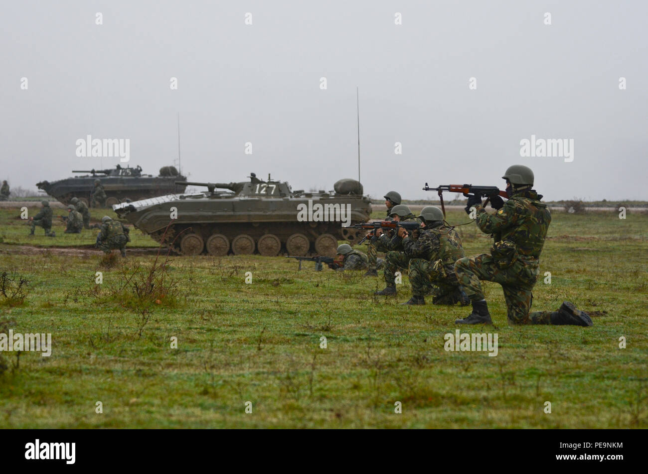 Bulgarian soldiers of 1-61st Mechanized Battalion get on line along the side of Boyevaya Mashina Pekhoty 1's (BMP -1) to suppress the enemy during Exercise Peace Sentinel at Novo Selo Training Center, Bulgaria, Nov. 24, 2015. (U.S. Army photo by Staff Sgt. Steven M. Colvin/Released) - Stock Image