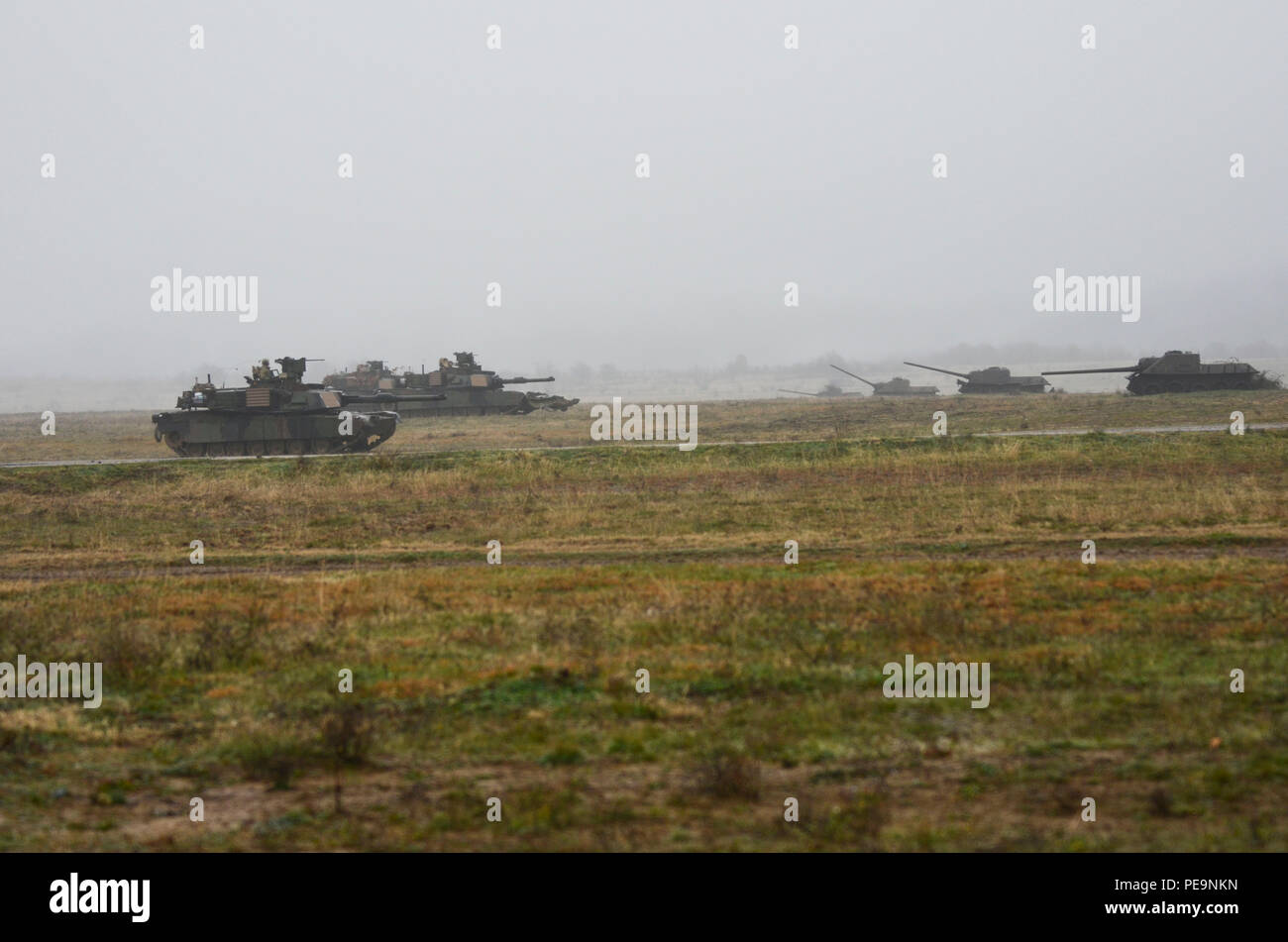Through the fog and the rain, U.S. Soldiers of 5th Squadron, 7th Cavalry Regiment, 3rd Infantry Division, stationed at Fort Stewart, Ga., drive M1A2 System Enhancement Package Version 2 Abrams tanks toward the enemy during Exercise Peace Sentinel at Novo Selo Training Center, Bulgaria, Nov. 24, 2015. Peace Sentinel is a joint exercise that focuses on interoperability between the Bulgarian and U.S. forces. The old tanks to the right are used as decoys and range targets. (U.S. Army photo by Staff Sgt. Steven M. Colvin/Released) - Stock Image