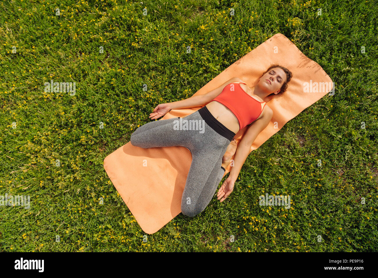 Dark-haired woman breathing slowly while finishing yoga class Stock Photo