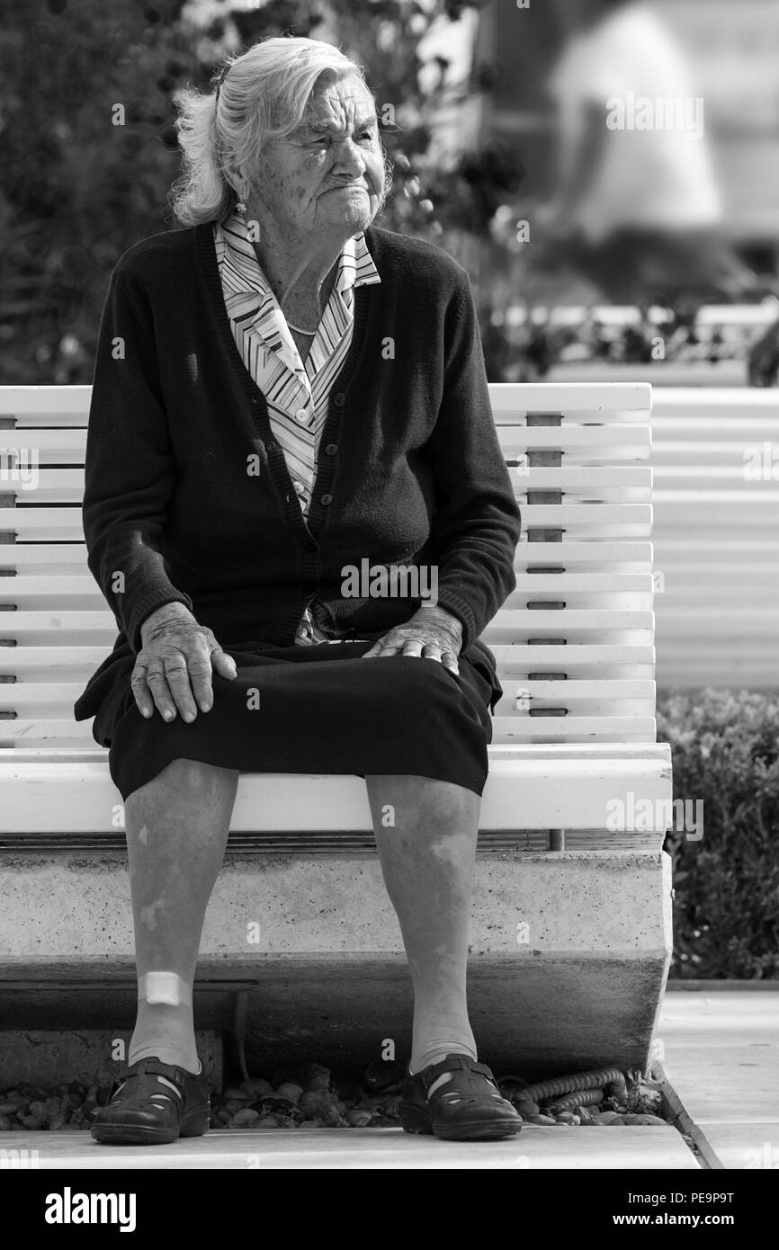 Old lady on a park bench, Obala Hrvatskog narodnog Preporoda, Split, Croatia: black and white version - Stock Image