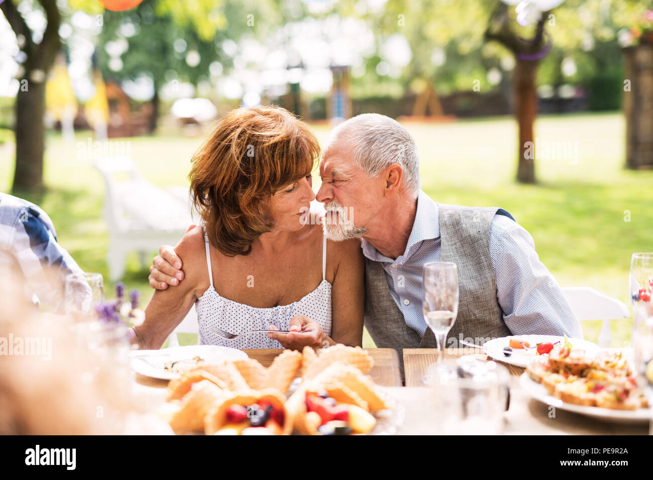 Senior couple sitting at the table on a garden party, touching noses. - Stock Image