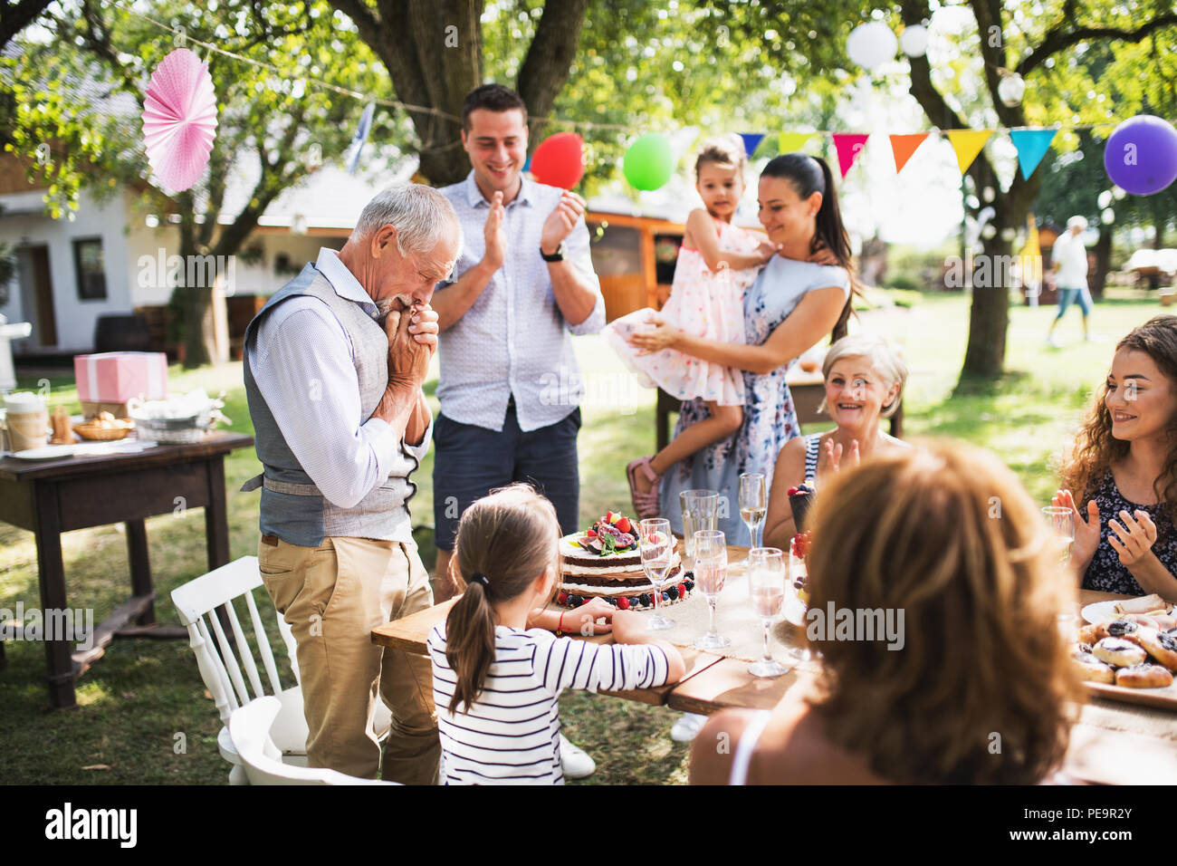 A senior man with an extended family looking at the birthday cake, crying. - Stock Image