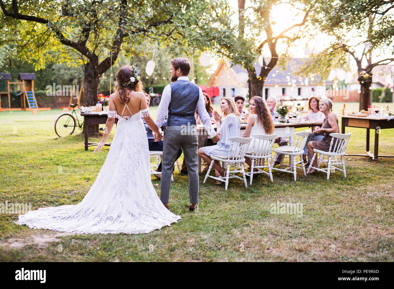 Bride And Groom Holding Hands At Wedding Reception Outside In The