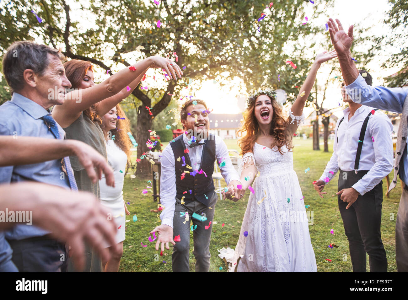 Bride, groom and guests throwing confetti at wedding reception outside. - Stock Image