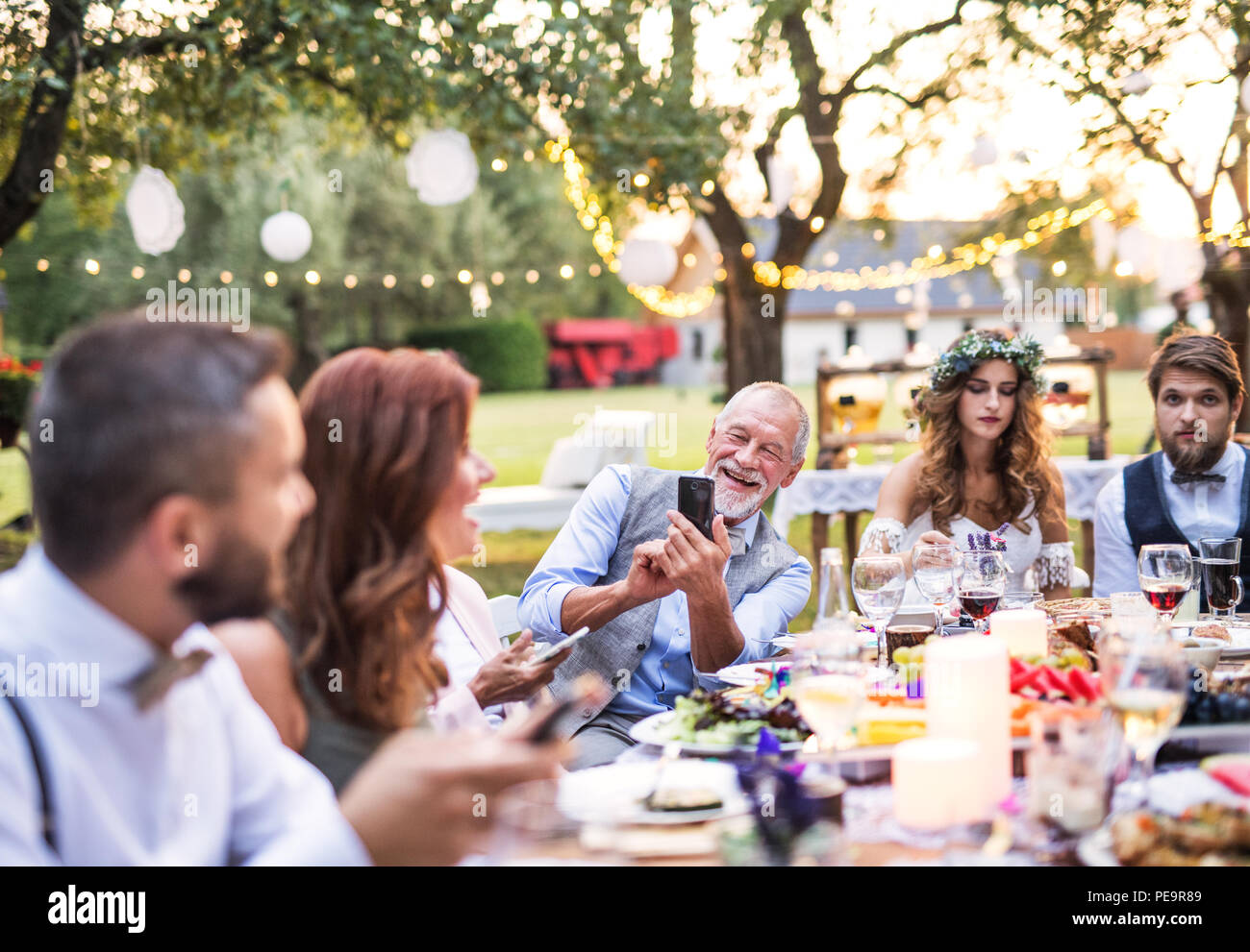 A senior man taking selfie at the wedding reception outside in the backyard. - Stock Image