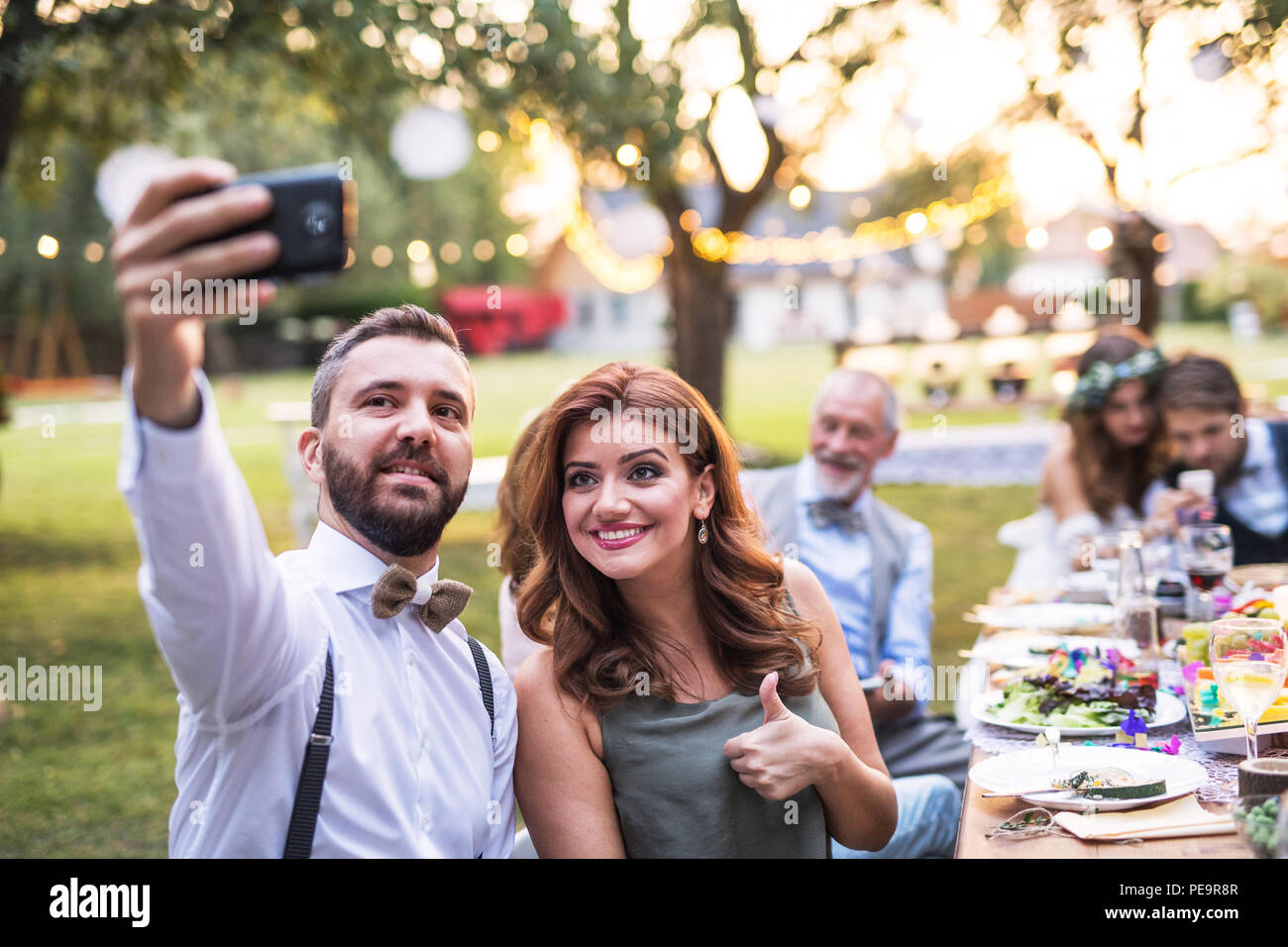 A couple taking selfie at the wedding reception outside in the backyard. Stock Photo